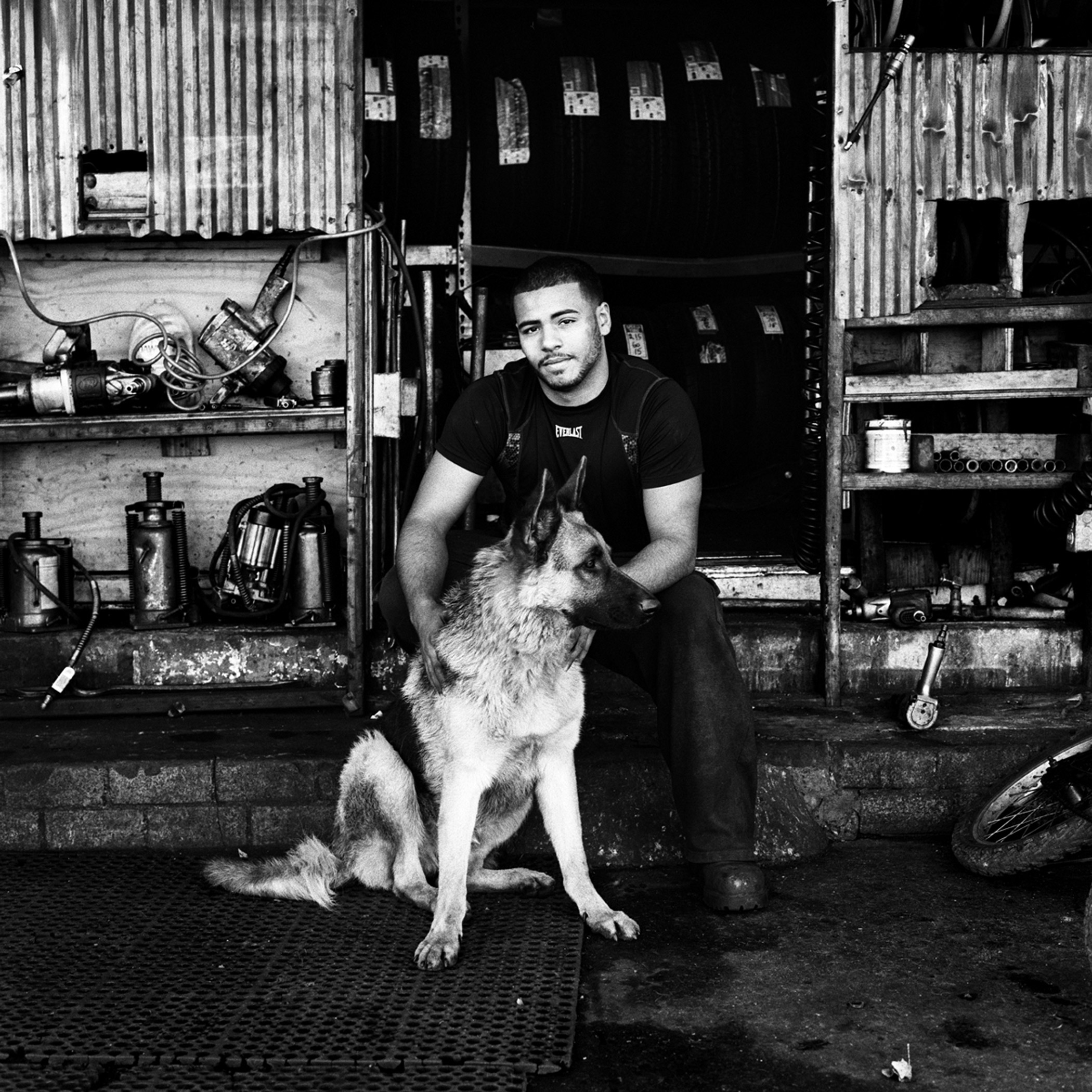 Anthony and his dog Riley at the entrance to their tire shop, P&J Tire Shop, on Metropolitan Avenue in Bushwick, Brooklyn, N.Y., November 2015.
