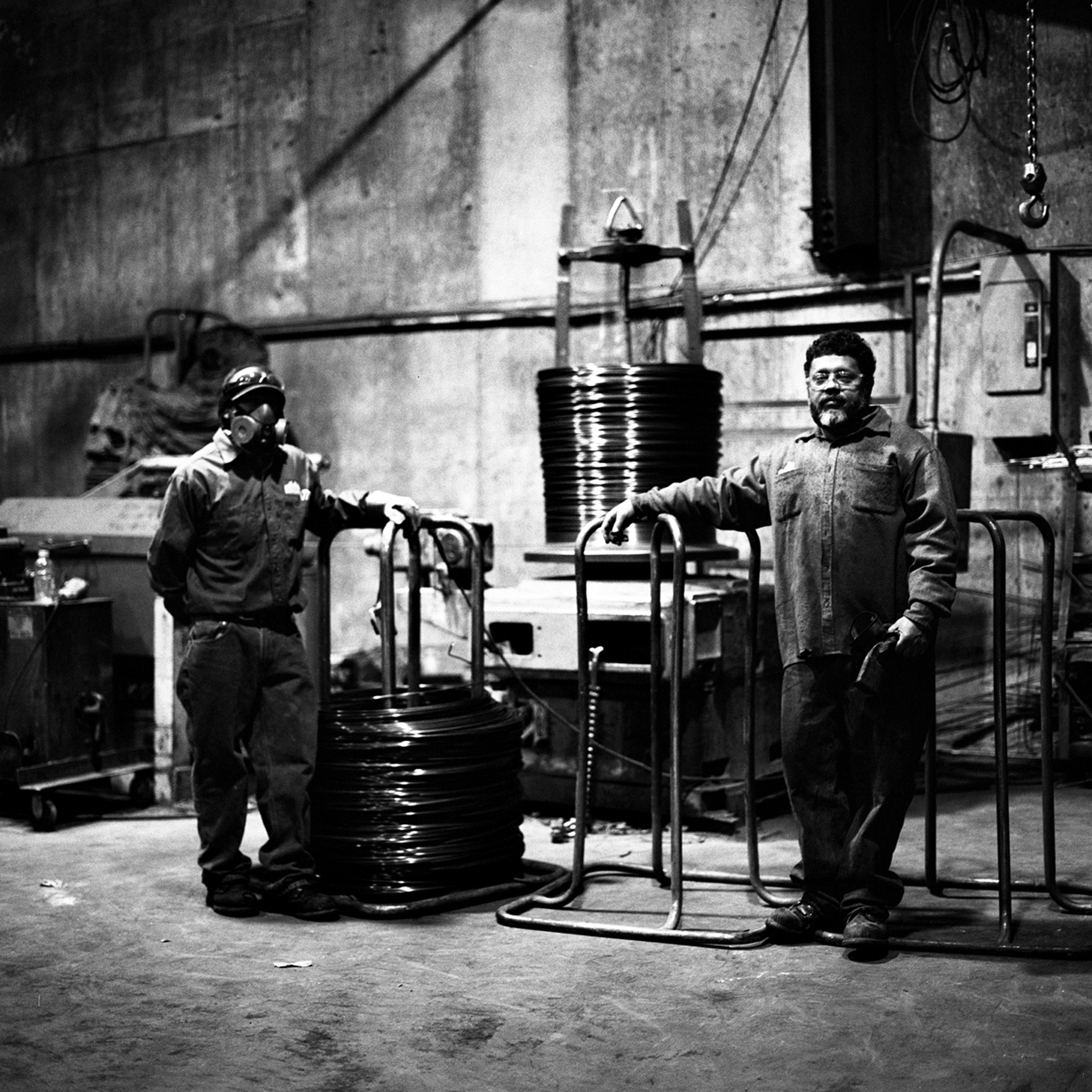 Angel, left, and Wilfredo by their post at the wire-straightener machine at Reinforcing Supply in Williamsburg, Brooklyn, N.Y., November 2015.
