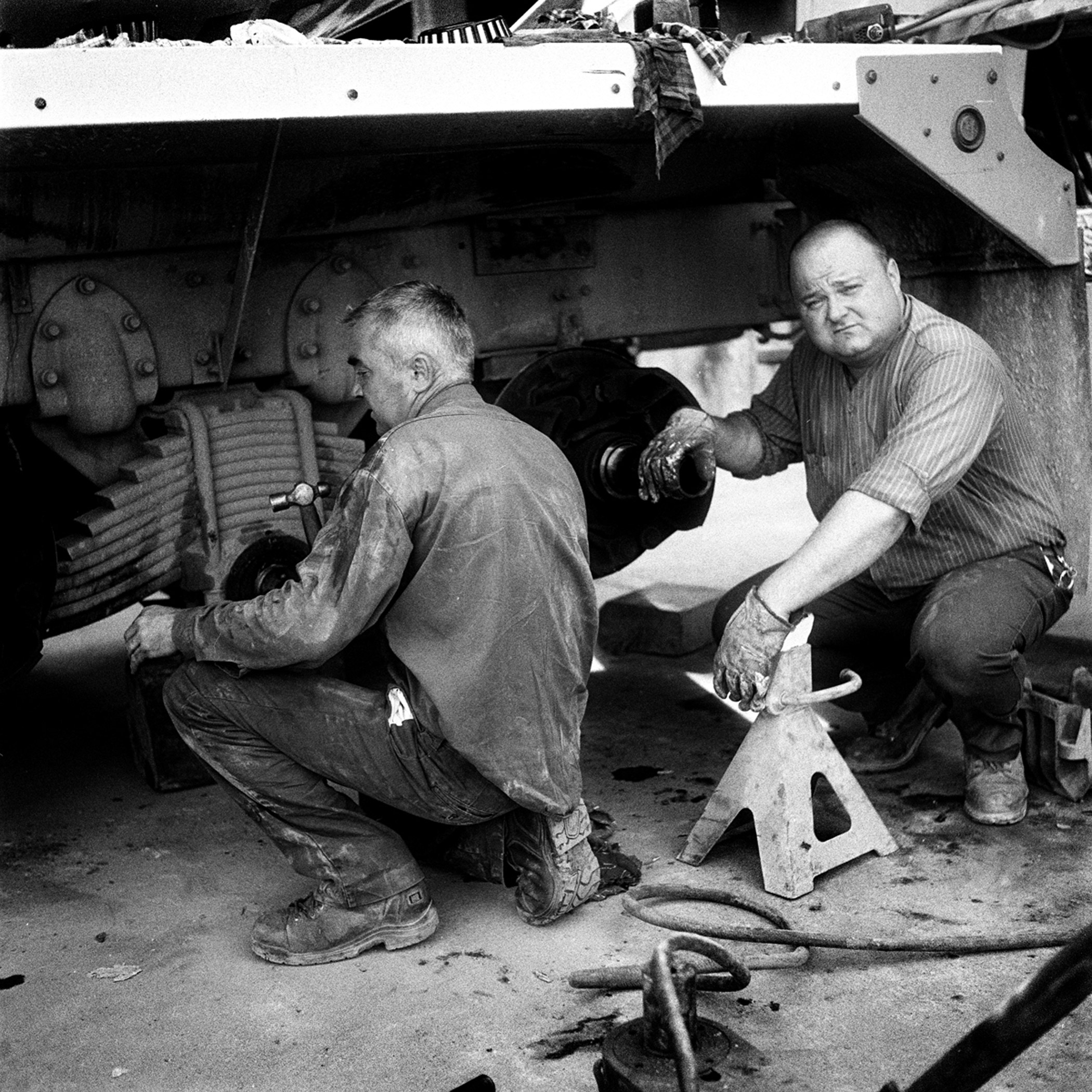 Slavic, on the suspension, and Carrol, in the support, work on one of the many Empire cement trucks that operate out of their depot on Maspeth Avenue in Williamsburg, Brooklyn, N.Y., July 2015.