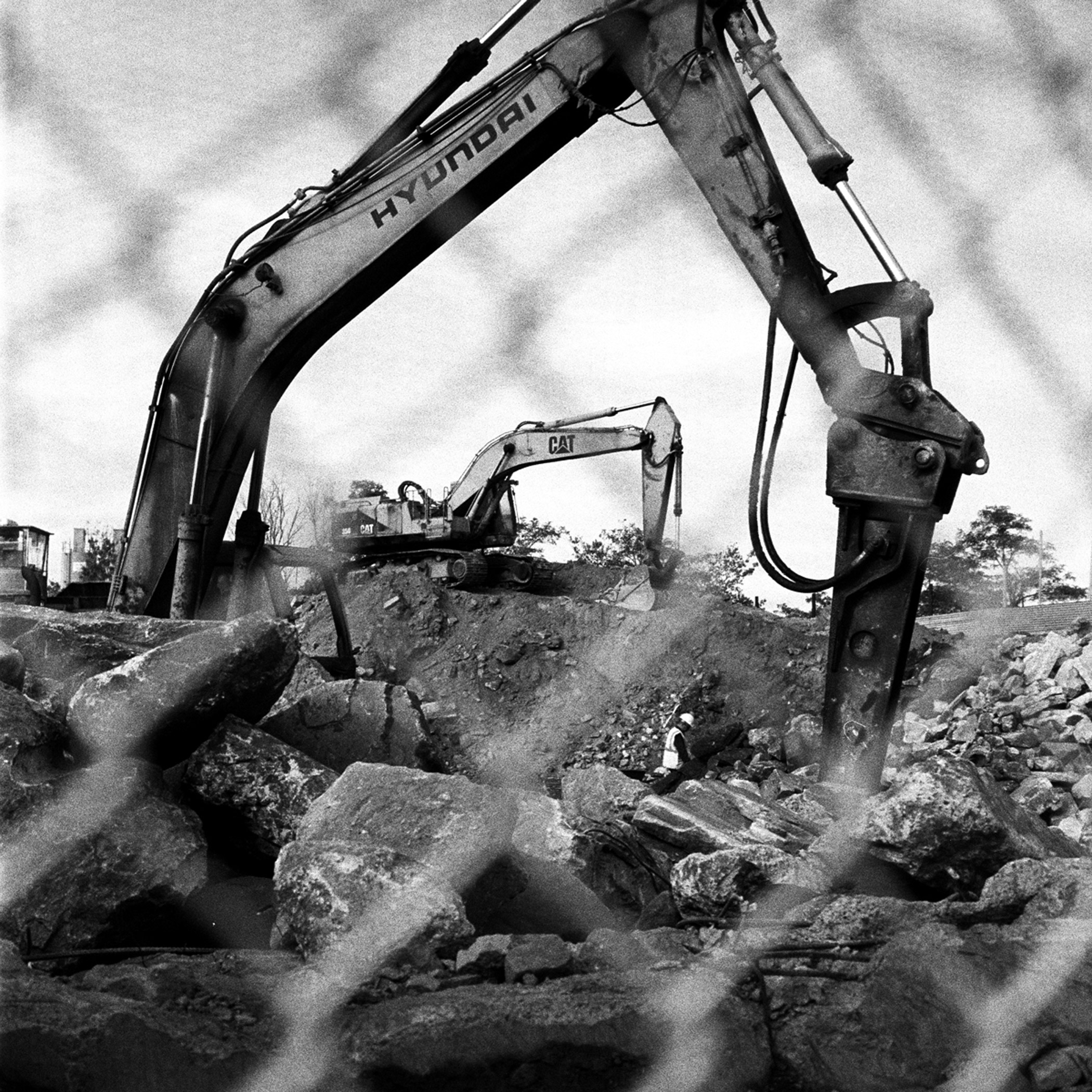 Workers between backhoe loaders break up old chunks of concrete and mince them into fine pebbles for reuse as filler on new concrete projects in Maspeth, Queens, N.Y., November 2015.