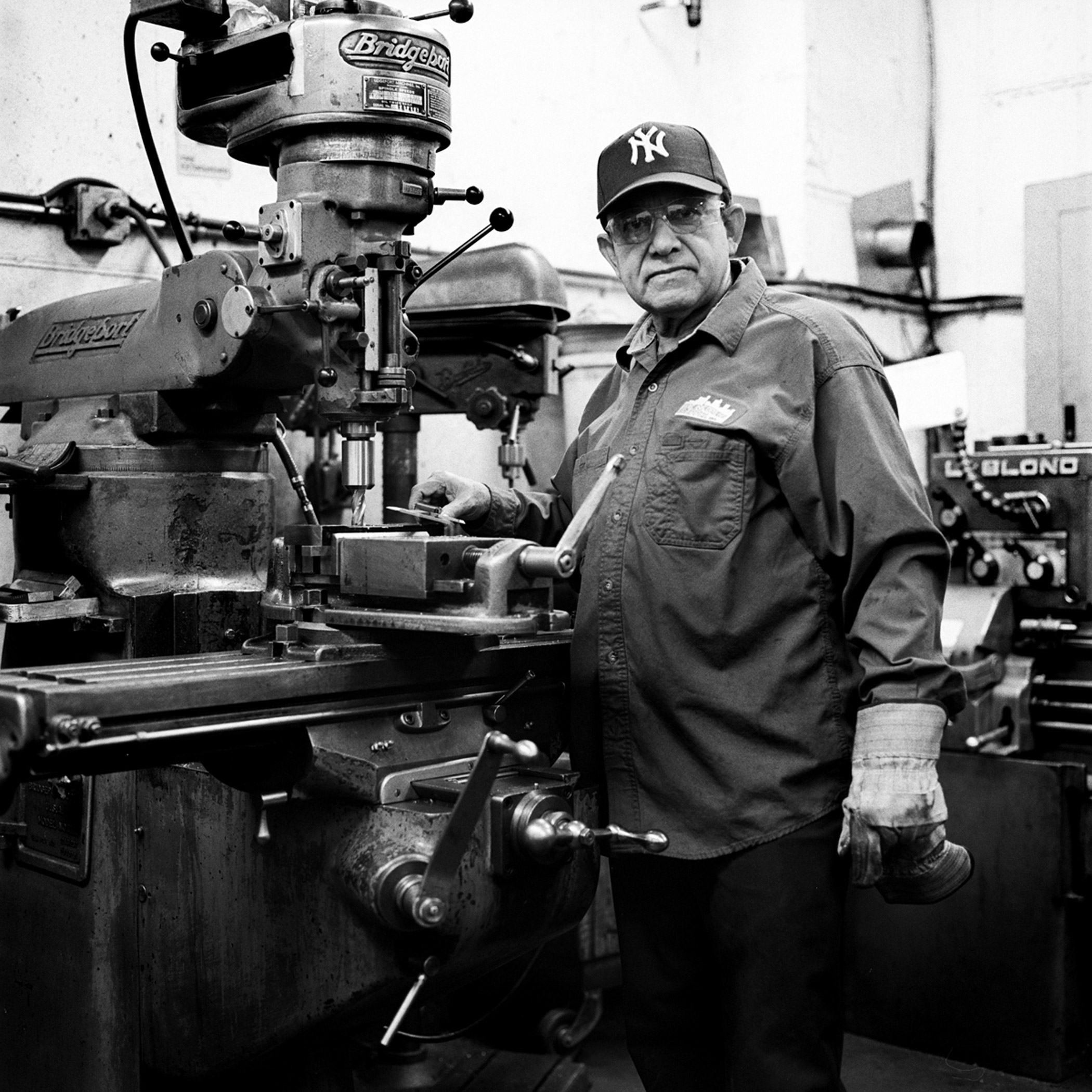 Mario, a machinist at Reinforcing Supply shop, stands with his driller in Williamsburg, Brooklyn, N.Y., November 2015.