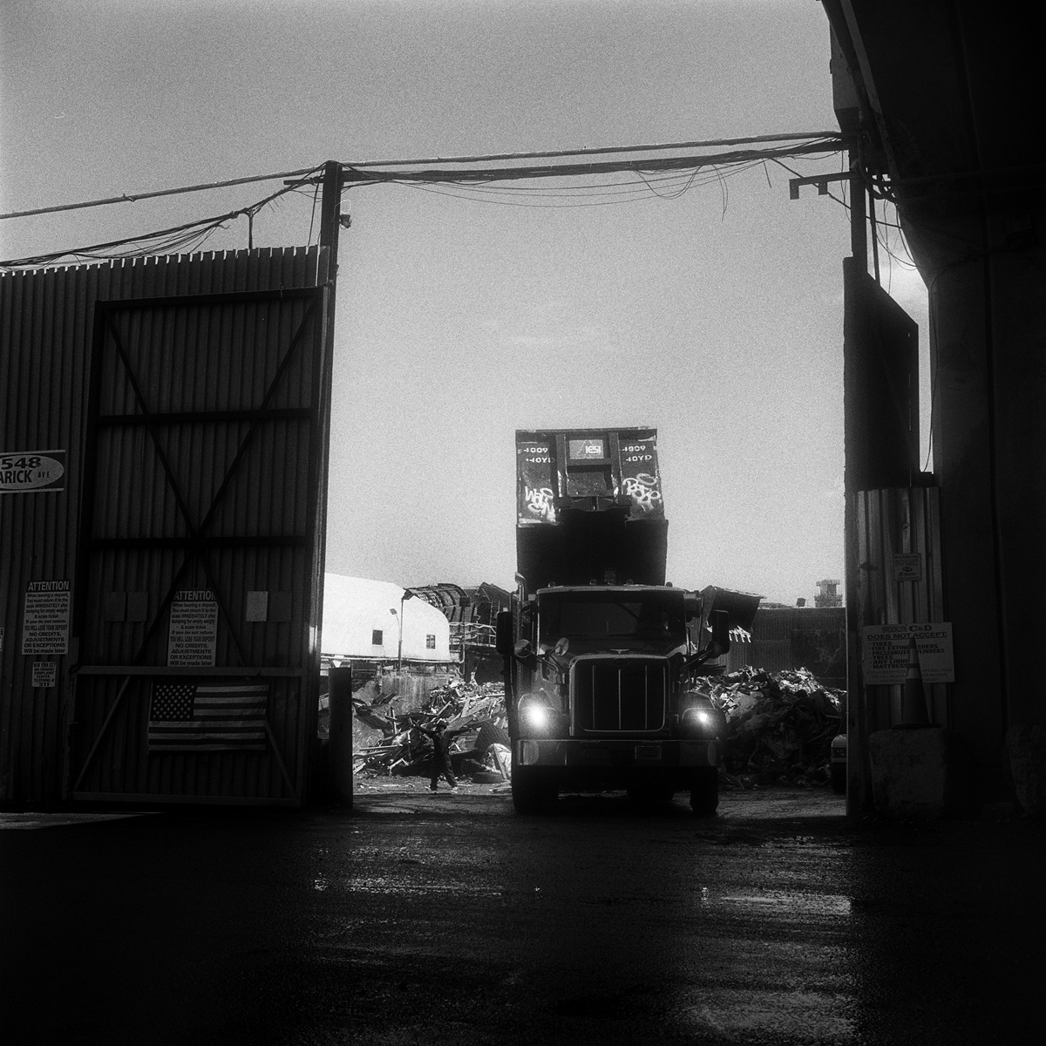 A roll-off truck with its container in the dumping position, as the yard spotter signals to the driver that his container is empty in Greenpoint, Brooklyn, N.Y., September 2015.