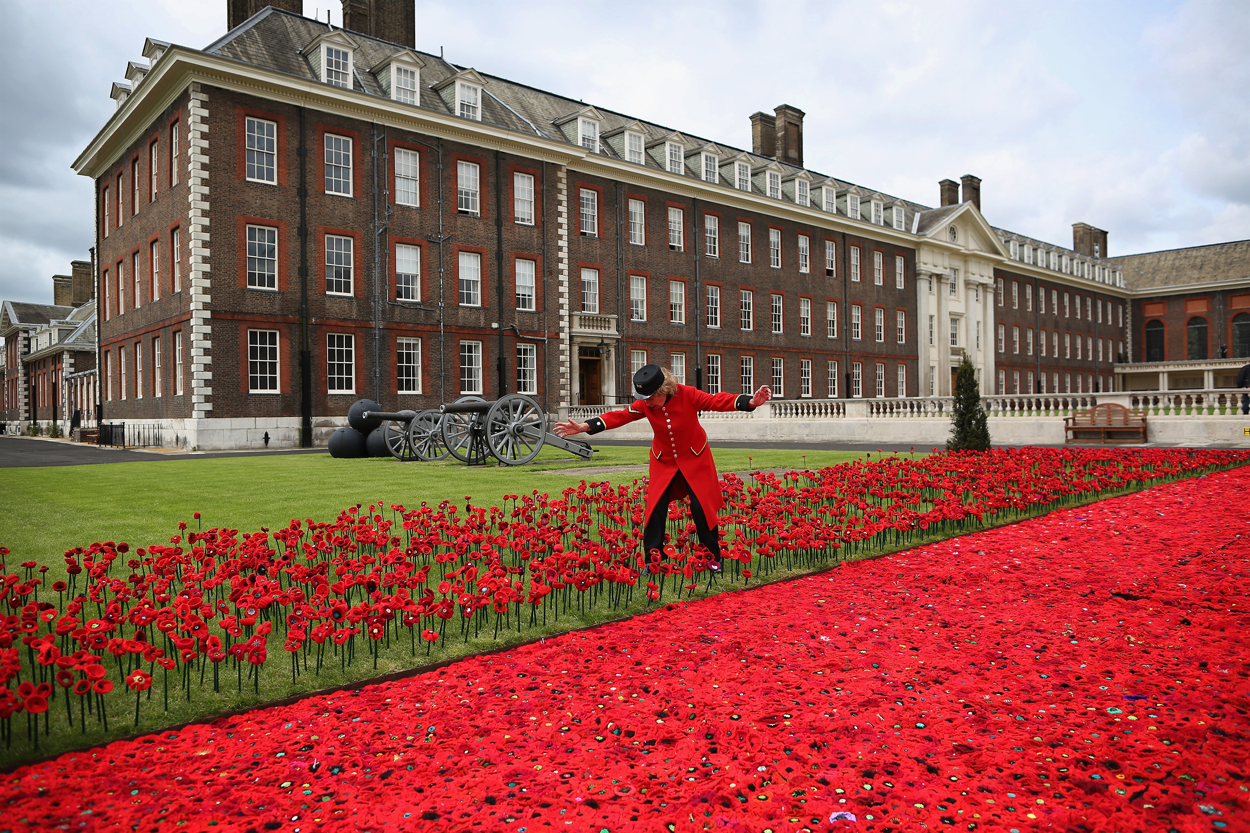 Chelsea Pensioner Gillian McDonald picks her way through an installation of Poppies while positioning herself for a photograph at Royal Hospital Chelsea in London on May 20, 2016.