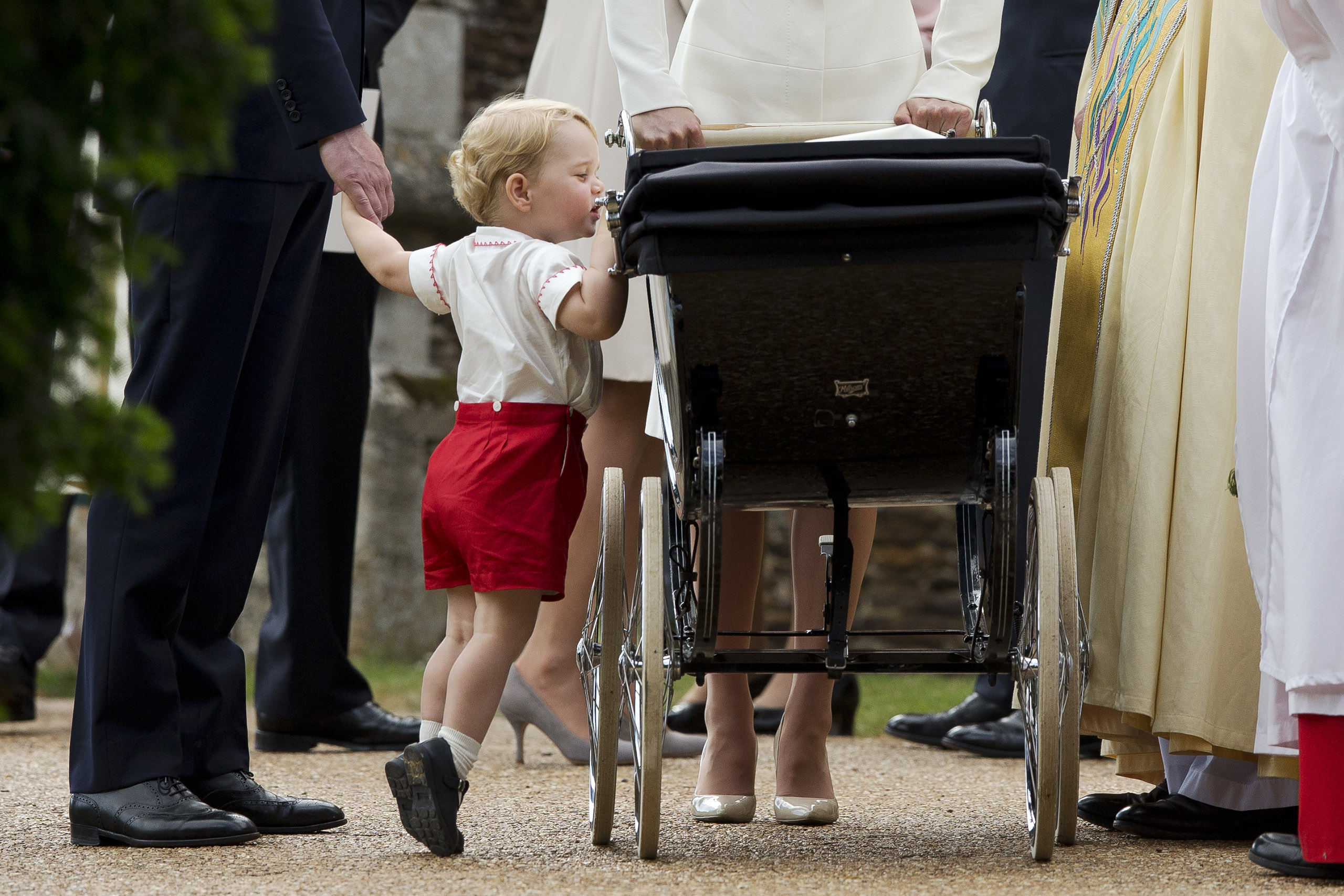 Catherine, Duchess of Cambridge and Prince William, Duke of Cambridge stand as Prince George of Cambridge looks into Princess Charlotte of Cambridge's pram as they leave the Church of St Mary Magdalene on the Sandringham Estate after the Christening of Princess Charlotte of Cambridge in King's Lynn, England on July 5, 2015.