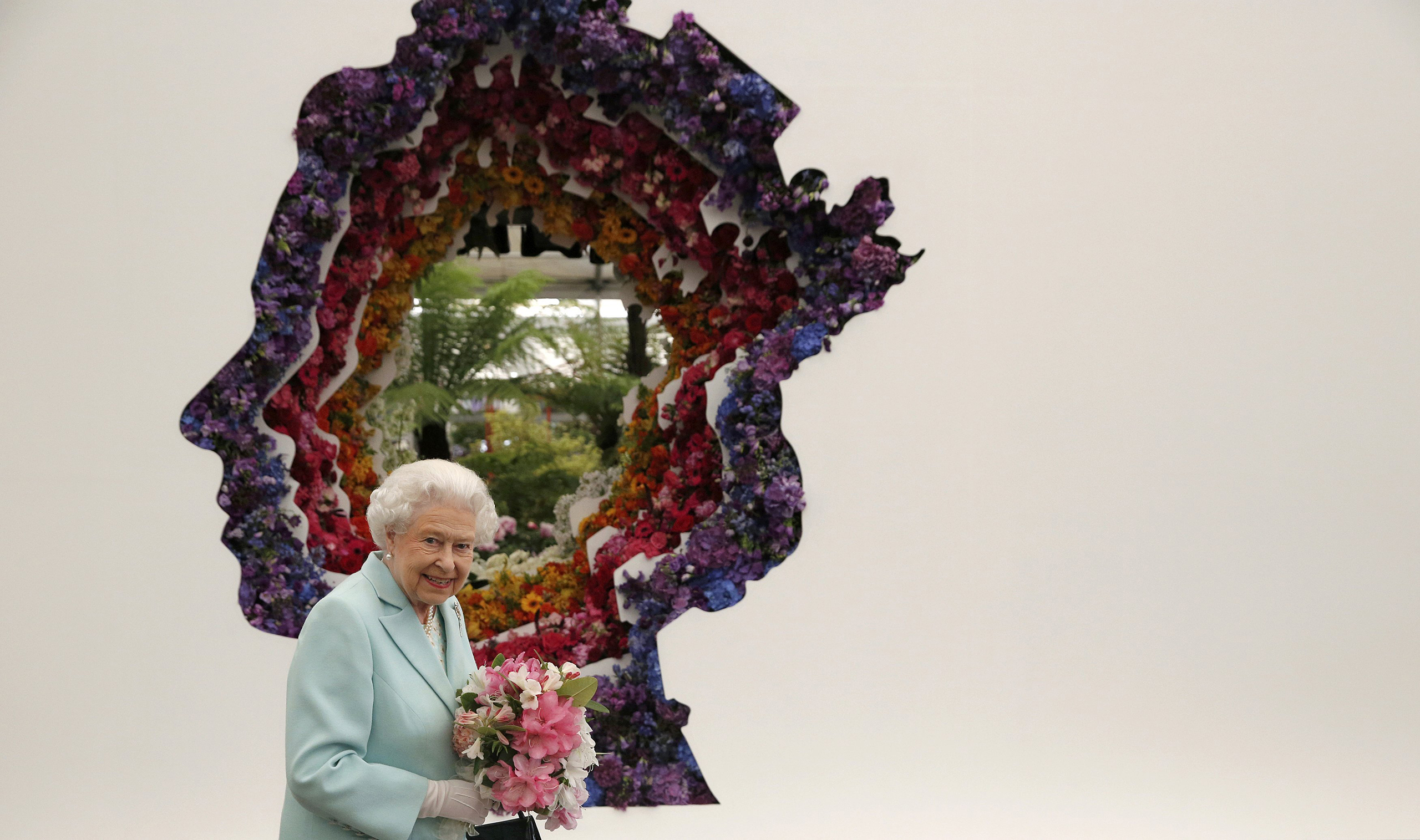 Queen Elizabeth II stands in front of a floral exhibit by the New Covent Garden Flower Market, which features an image of the Queen at the Chelsea Flower Show in London, May 23, 2016.