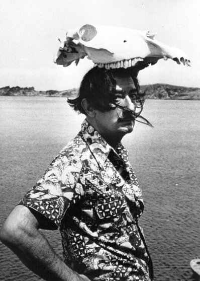 Salvador Dali wearing an animal skull as a hat. 1950.