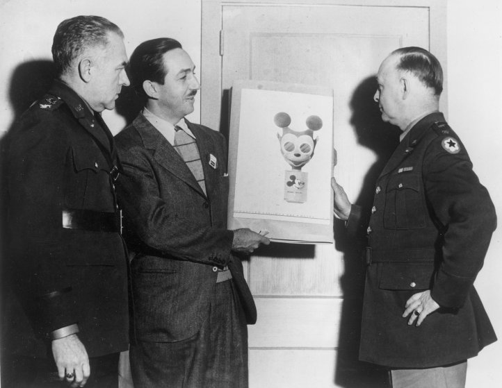 Animator Walt Disney, second from left, hands over his sketch of a Mickey Mouse gas mask to Maj. Gen. William Porter, right, in Washington, D.C., Jan. 8, 1942. Civilian defense and chemical warfare officers plan to produce the design intended to encourage children to use their mask readily for protection during World War II.