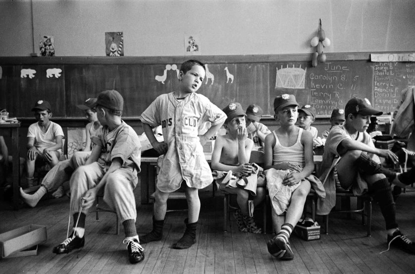In a kindergarten classroom, baseball players try on new uniforms as Dick Williams (center) and others anxiously await missing parts of outfits, 1954.