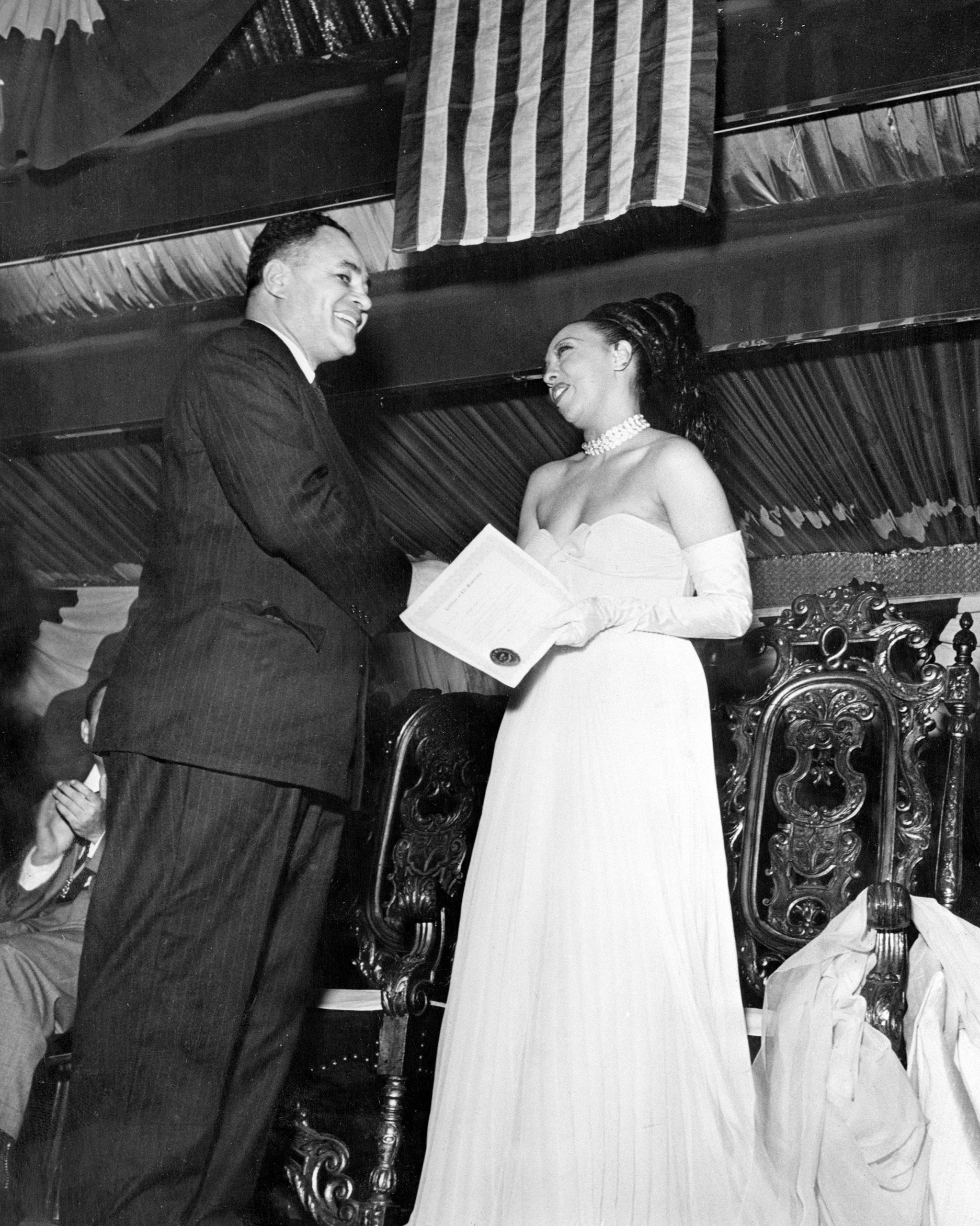 Dr. Ralph Bunche, former Palestine mediator and now director of United Nations trusteeship, serves as honorary chairman of  Jo Baker Day  honoring the well-known singer and entertainer. Dr. Bunche is shown presenting Miss Baker with Life Membership in the New York Branch of the NAACP, the sponsoring organization. 1950.