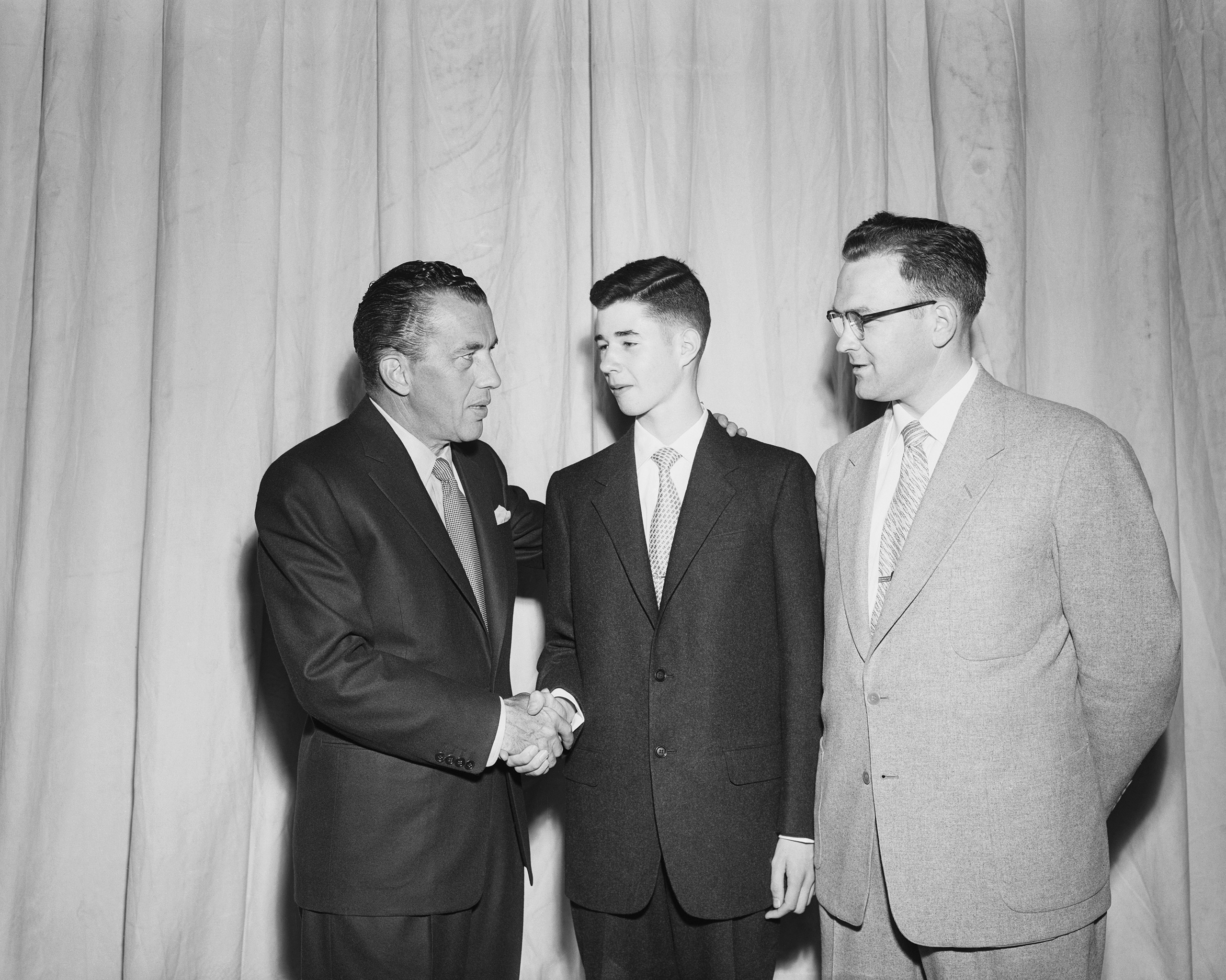 Fourteen-year-old eighth grader William Cashore of Norristown, Pennsylvania, gets congratulated by television personality Ed Sullivan. (Right: Willard Widerberg, selected Teacher of the Year by the National Education Association.)