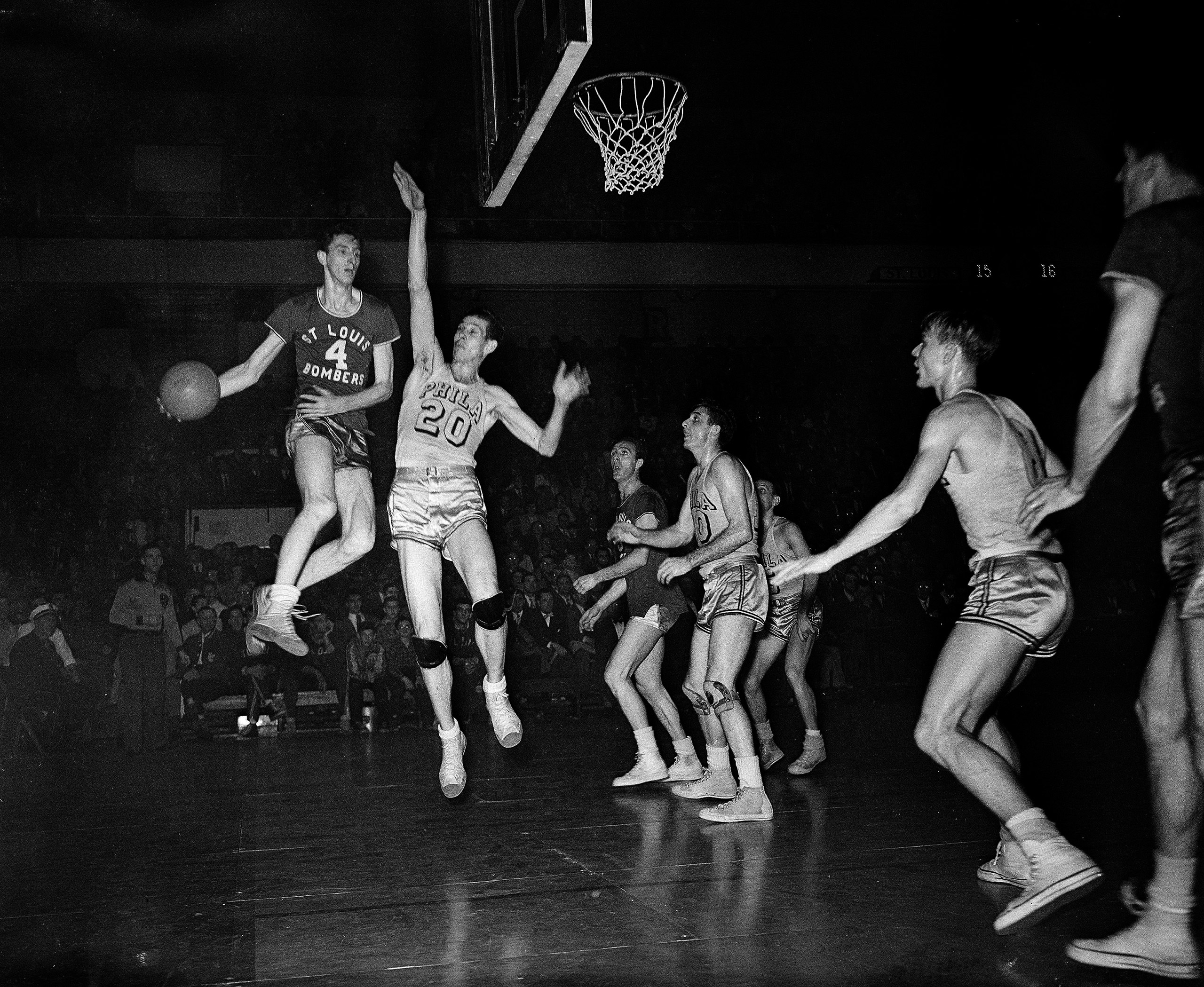 Red Rocha (4), St. Louis Bombers center, goes up in the air to make a pass in Basketball Association of America playoff game with the Philadelphia Warriors at the Arena, March 30, 1948. Chuck Halbert, lanky Warriors center, also leaves the floor in an attempt to block the pass.