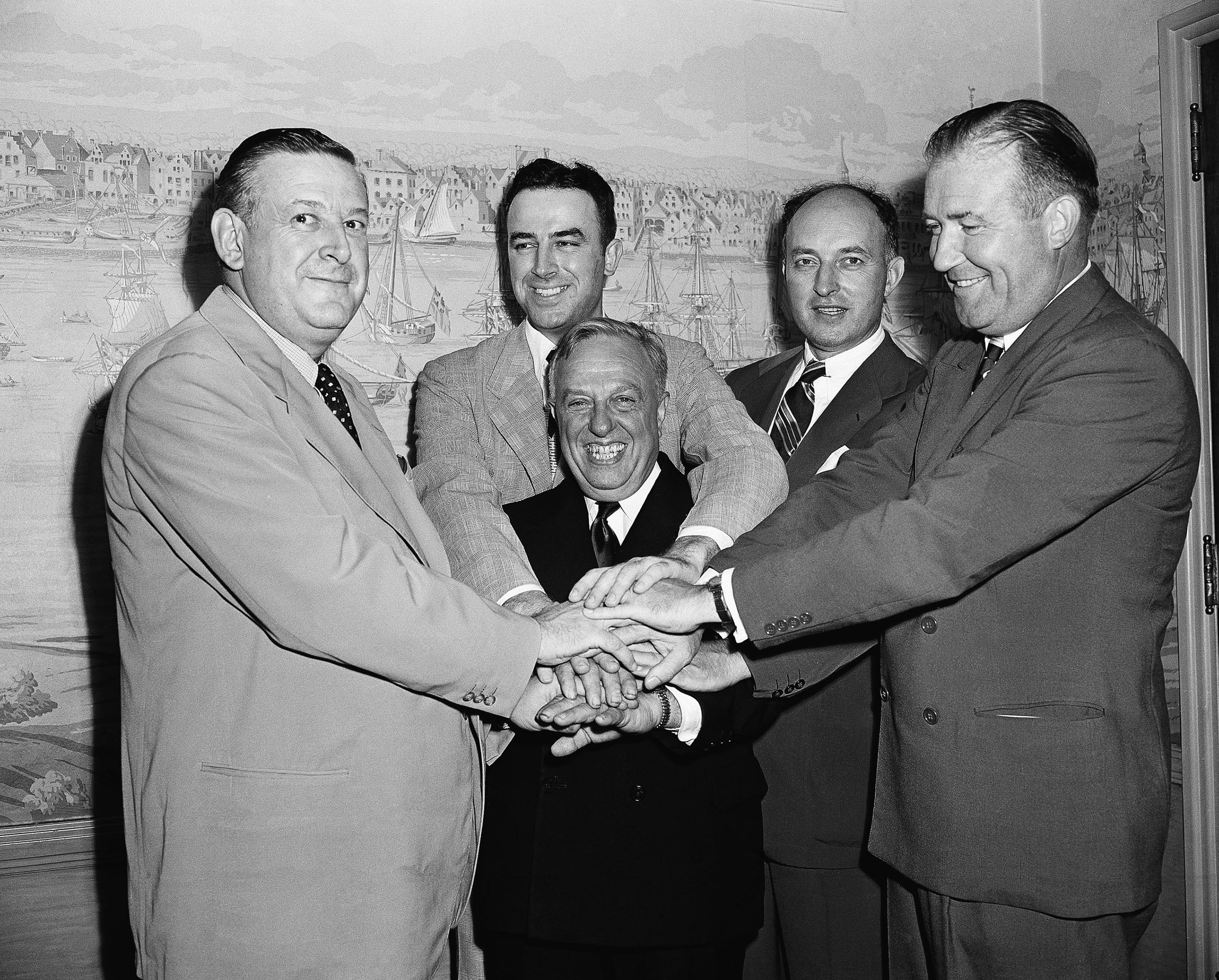 Representatives of the National Basketball League and Basketball Association of America, shake hands after agreeing to a merger of the two circuits into an 18-team organization to be known as the National Basketball Association, Aug 3, 1949, New York. Grouped around the smiling Maurice Podoloff, center, are left to right: Ike Duffey, Leo Ferris, Ned Irish, and Walter Brown.