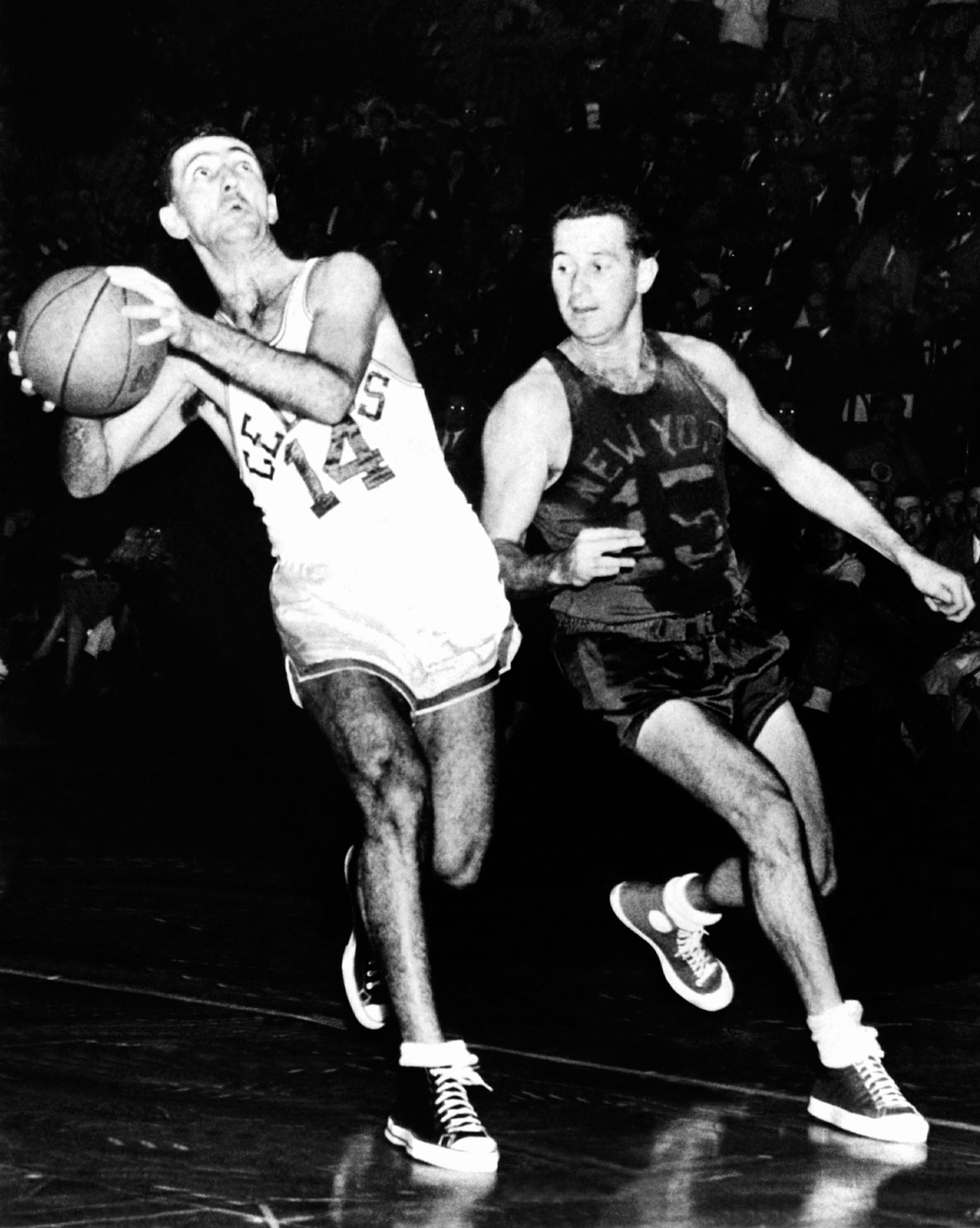 Bob Cousy #14 of the Boston Celtics drives to the basket against Dick McGuire #15 of the New York Knicks at the Boston Garden circa 1950 in Boston.