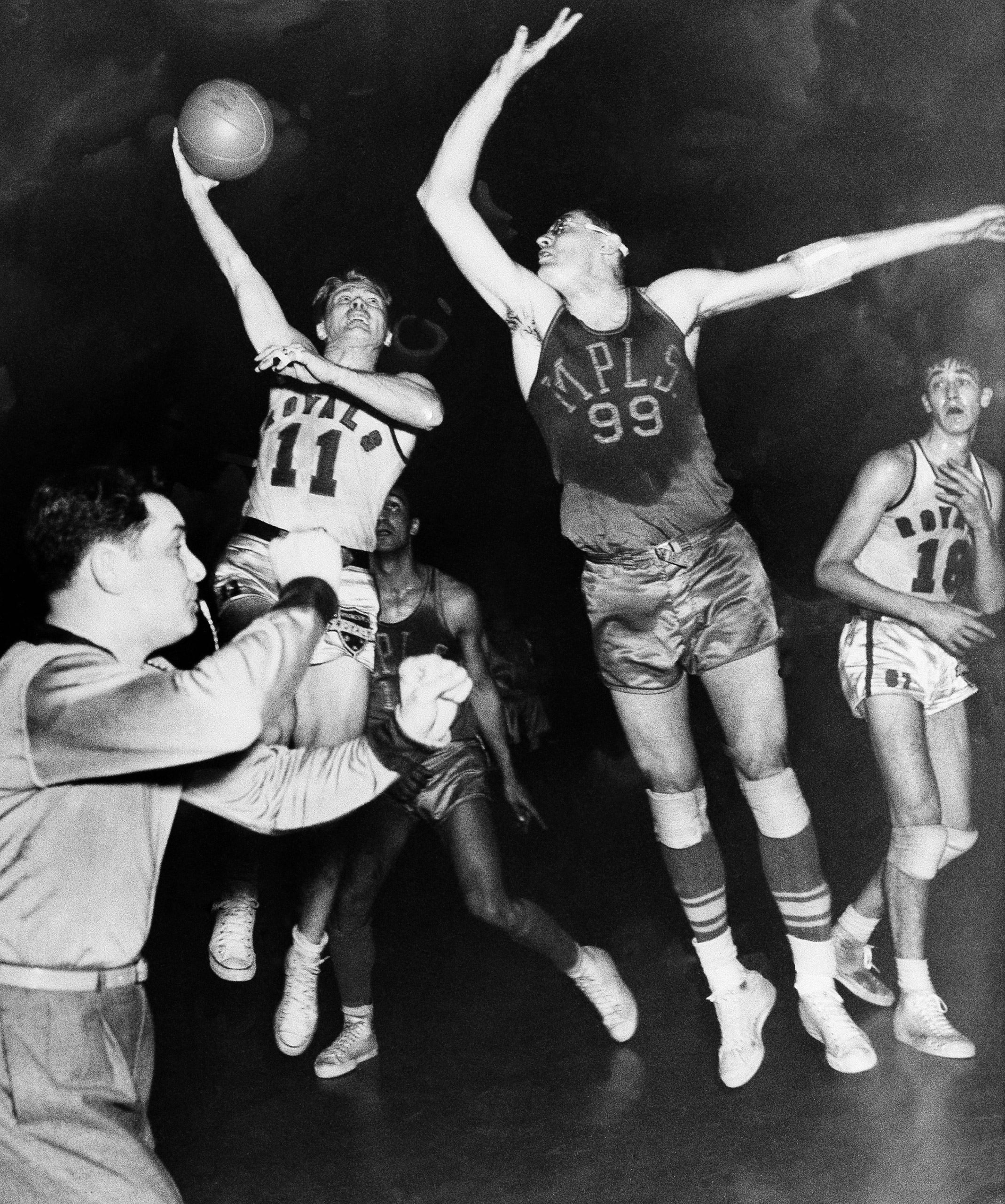 George Mikan (99), star Minneapolis Lakers center, breaks up a shot by Bob Davies, Rochester Royals guard (11) in the decisive game of the National Basketball Association's Western Division playoffs,  April 4, 1951 in Rochester, N.Y. Rochester, won, 80-75.