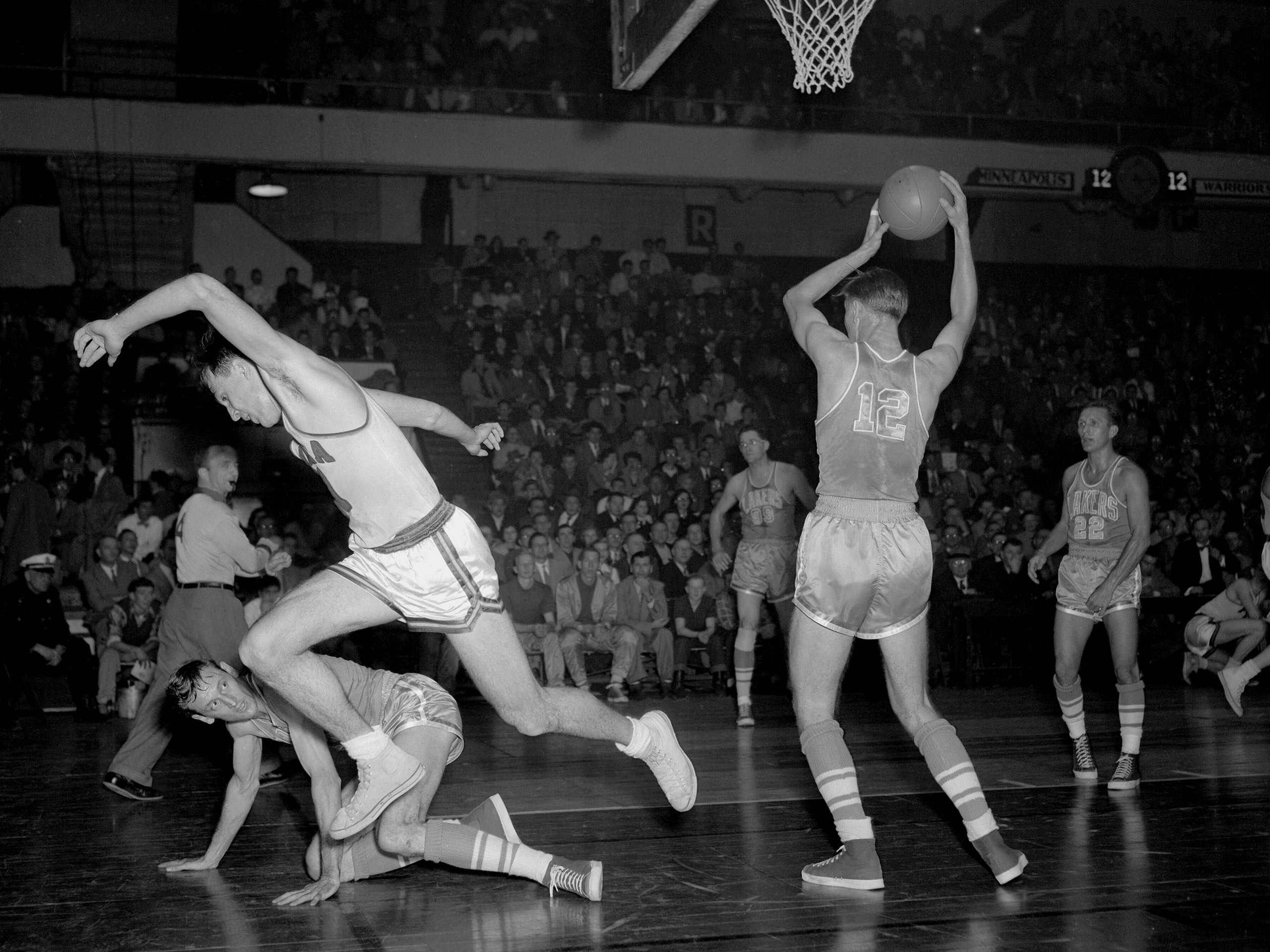 Howie Schultz #12 of the Minneapolis Lakers rebounds against the Philadelphia Warriors on Dec. 21, 1951 at the Philadelphia Civic Center in Philadelphia.