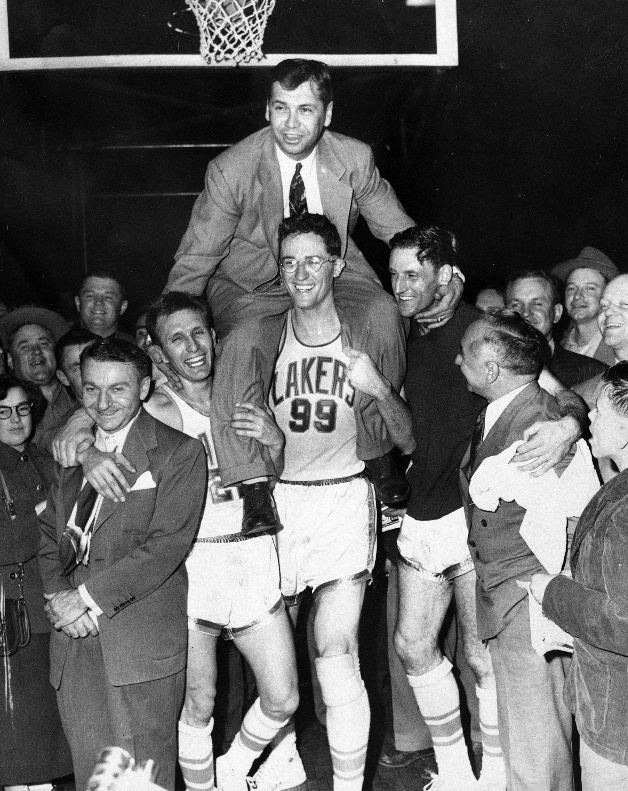 Minneapolis Lakers hoist coach John Kundla and carry him to their dressing room after beating the New York Knickebockers 82-65 April 25, 1952, and winning their fourth  National Basketball Association title  in five years.