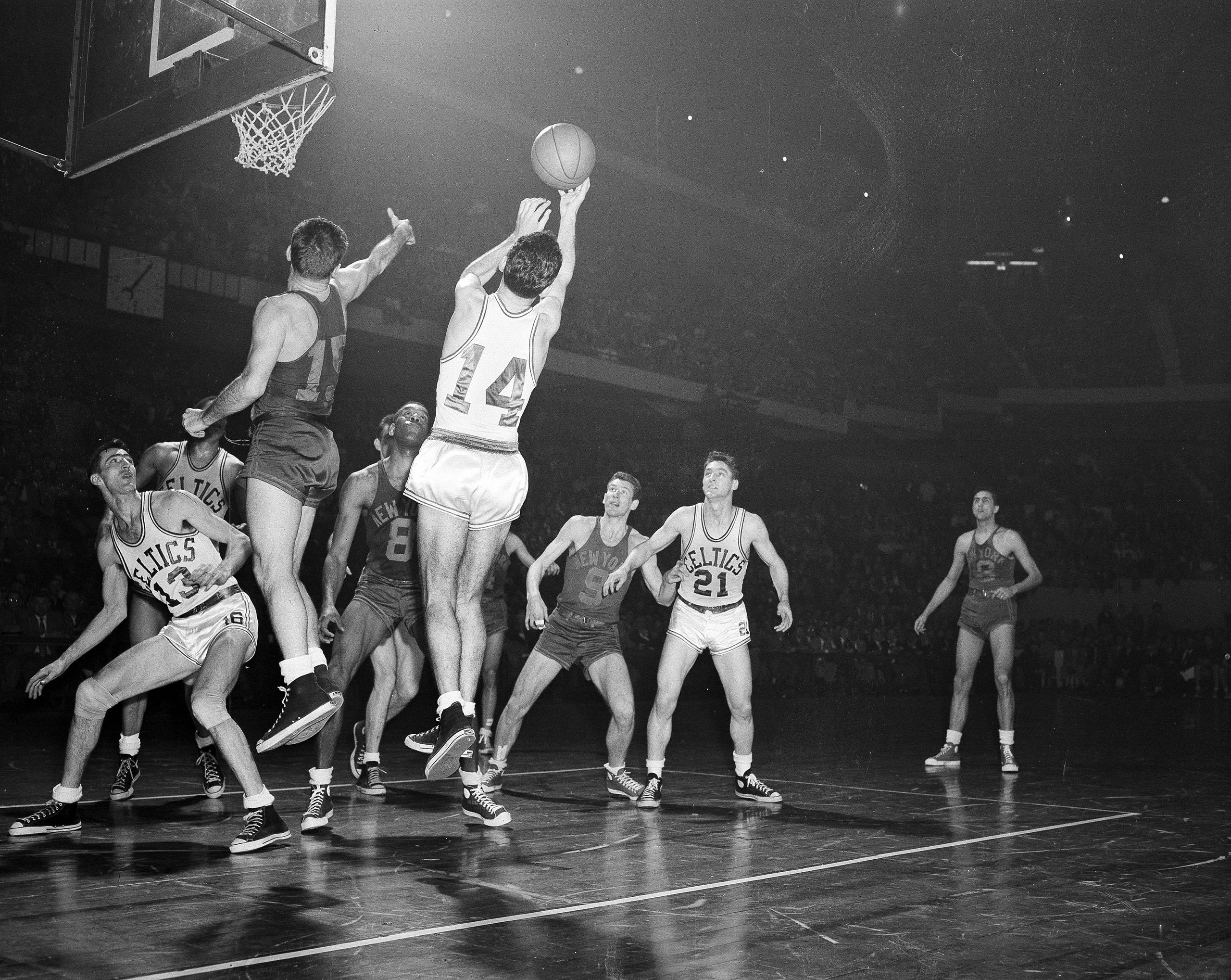 Bob Cousy (14) of the Boston Celtics takes a rebound off the backboard after an attempted basket by Dick McGuire (15) of the New York Knickerbockers in the fourth quarter of their NBA playoff game at the Boston Garden in Boston, March 26, 1953.