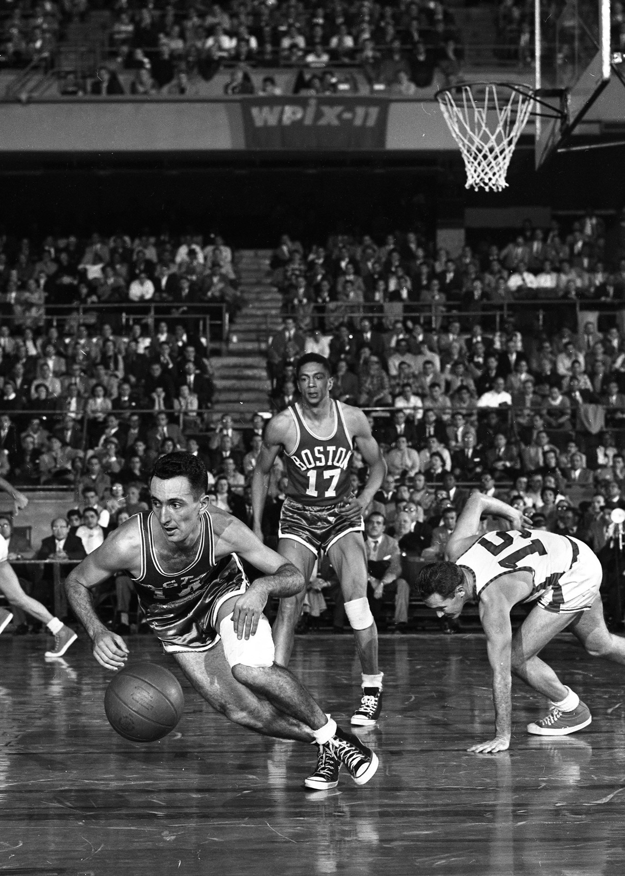 Dick McGuire (right) drops to knee as Boston's Bob Cousy outslicks him during fourth period action at Garden. Alan Barksdale (center) seems awed by teammate Cousy's daring, but things evened up for Knicks as they pulled away to 88-83 victory. Circa 1955.