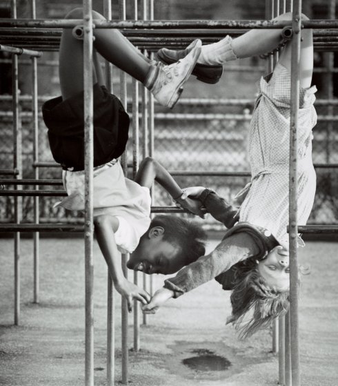 Two schoolgirls holding hands as they hang upside down from a jungle gym. Circa 1940s.