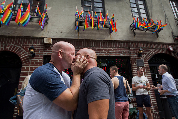 Doug Mest, left, and Mark Pelekakis, second left, of Los Angeles, kiss outside the Stonewall Inn after the U.S. Supreme court ruling in New York, U.S., on Friday, June 26, 2015. Same-sex couples have a constitutional right to marry nationwide, the U.S. Supreme Court said in a historic ruling that caps the biggest civil rights transformation in a half-century.