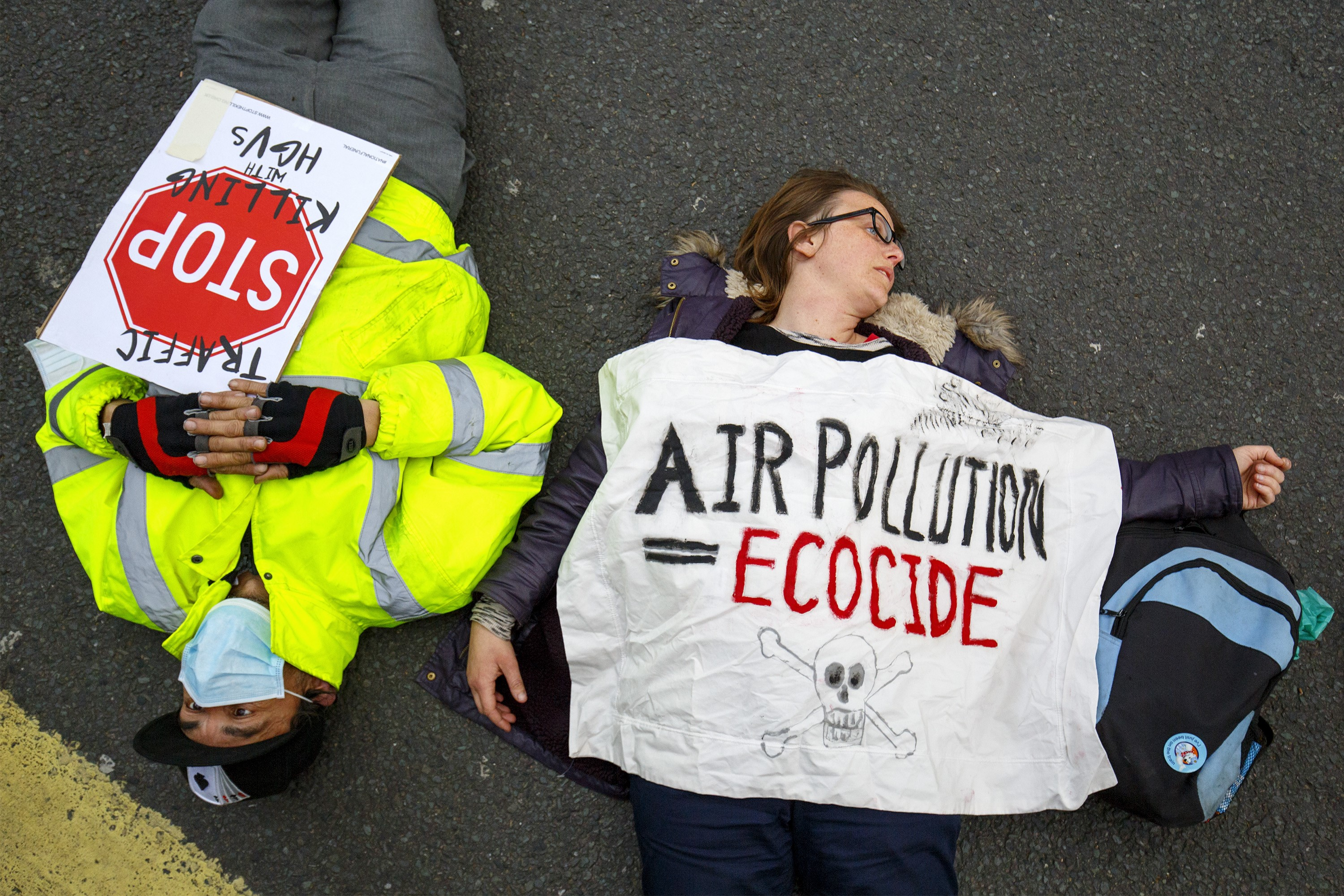 Protesters stage a die-in protest with gas masks and teddy bears at an antipollution rally outside the Department for Transport in London to highlight the dangers of polluted air poses to people and children's health on April 27, 2016