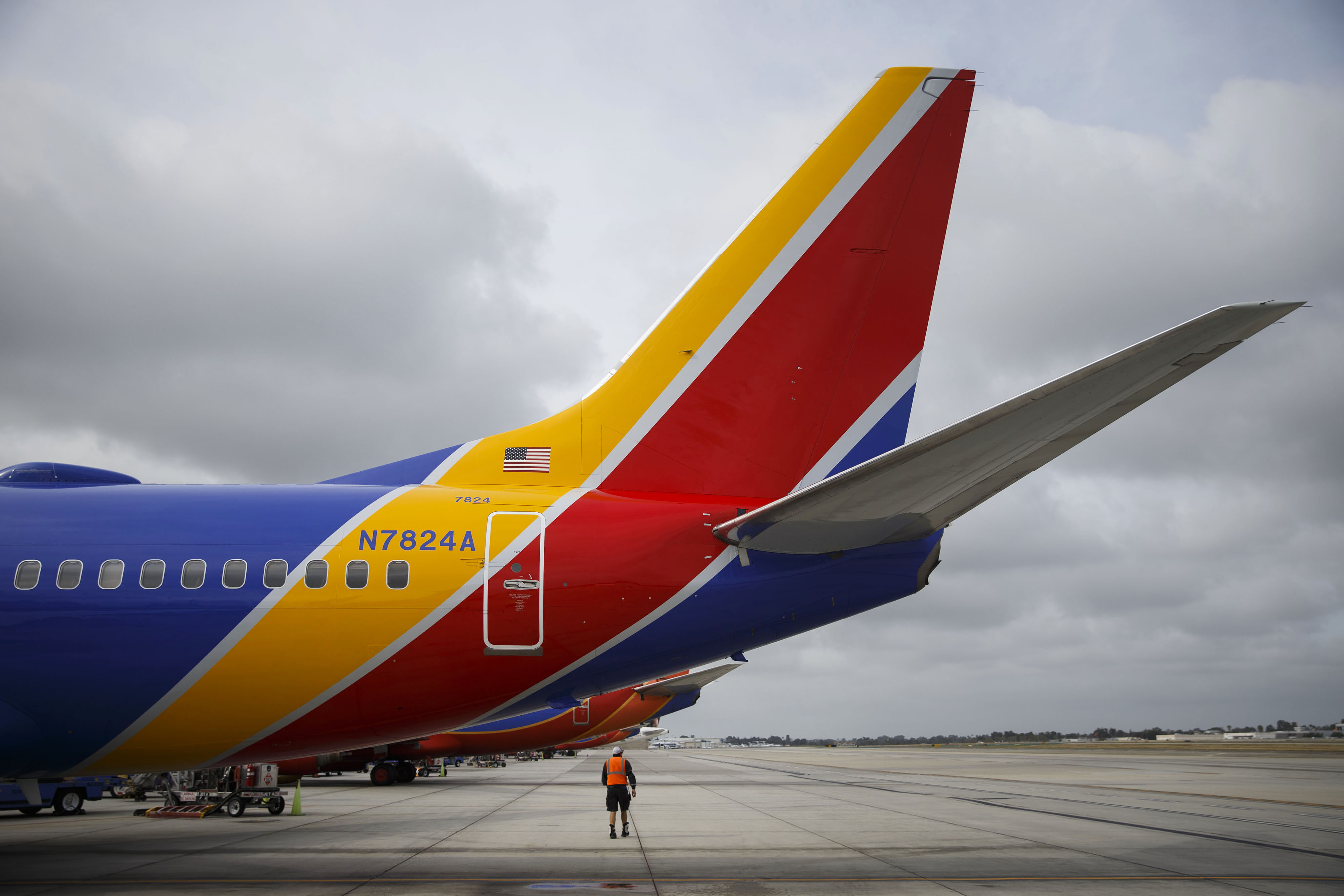 A Southwest Airlines Co. employee walks underneath the tail of a Boeing Co. 737 aircraft on the tarmac at John Wayne Airport (SNA) in Santa Ana, California, on April 14, 2016.