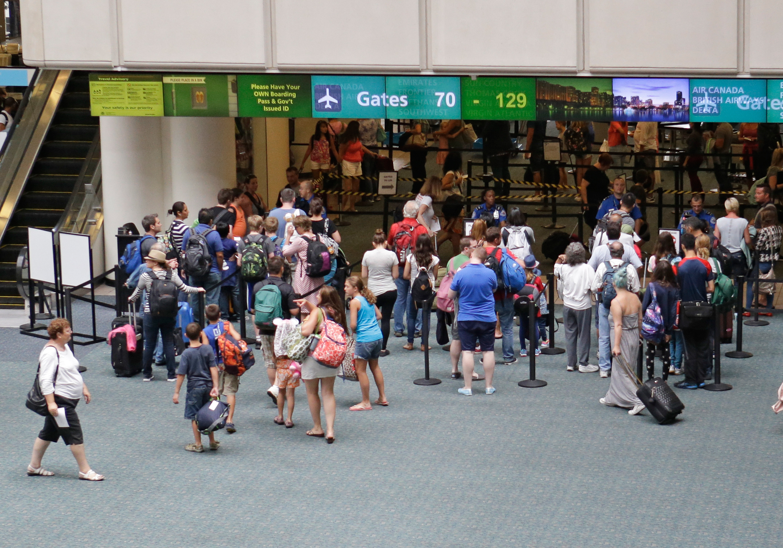 In this Monday, Aug. 31, 2015 photo, passengers line up at security check points before heading to their departure gates at Orlando International Airport in Orlando, Fla. The state's second-busiest airport has embarked on a $1.1 billion expansion, the largest in two decades, for a new garage, check-in kiosks and a train terminal to service the privately funded All Aboard Florida line which will run from Orlando to Miami in two years. (AP Photo/John Raoux)