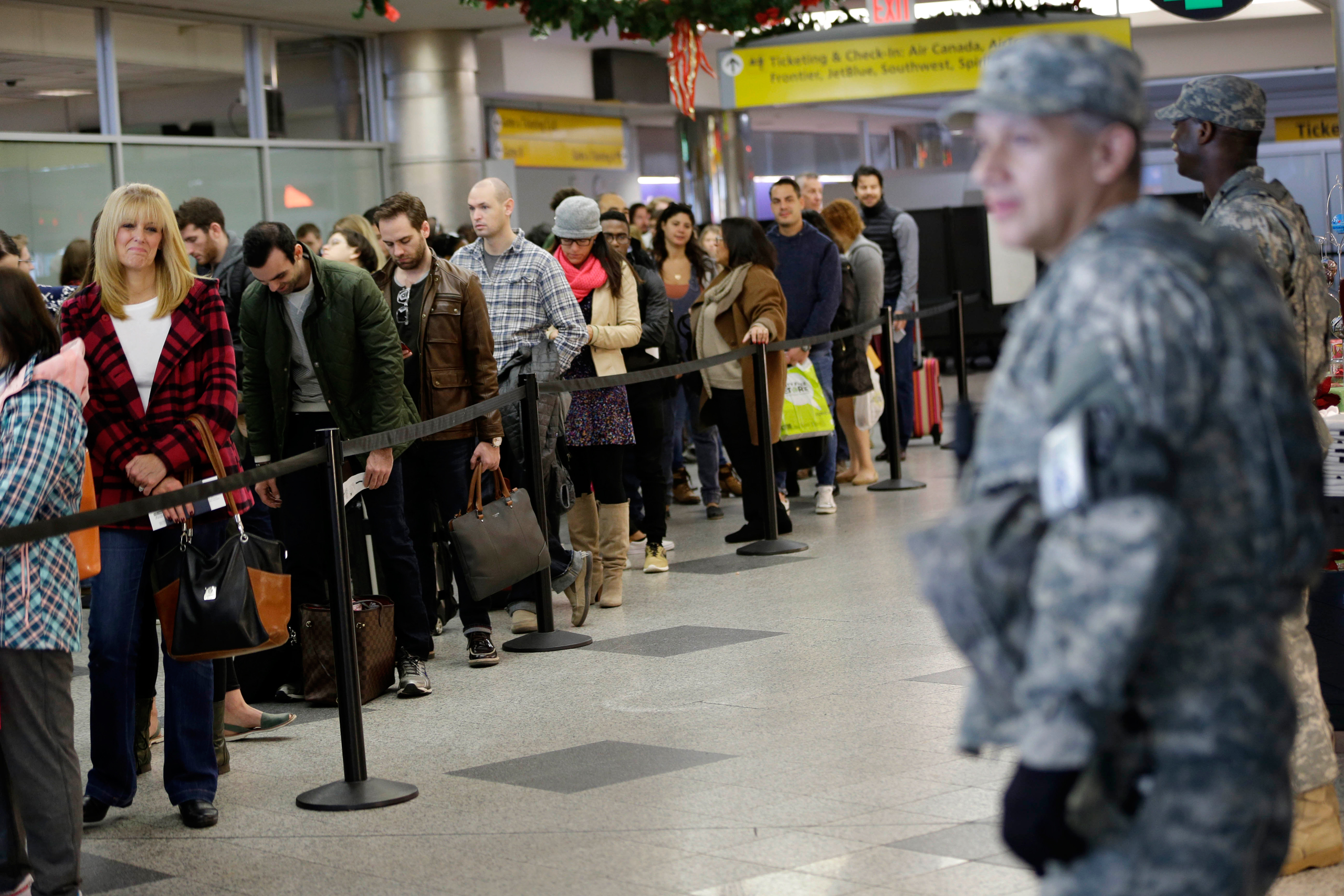 Security personnel looks on as passengers wait to pass through airline security at LaGuardia Airport in New York, Wednesday, Nov. 25, 2015. An expanded version of America's annual Thanksgiving travel saga was under way Wednesday with gas prices low and terrorism fears high. An estimated 46.9 million Americans are expected to take a car, plane, bus or train at least 50 miles from home over the long holiday weekend, according to the motoring organization AAA. That would be an increase of more than 300,000 people over last year, and the most travelers since 2007. (AP Photo/Seth Wenig)