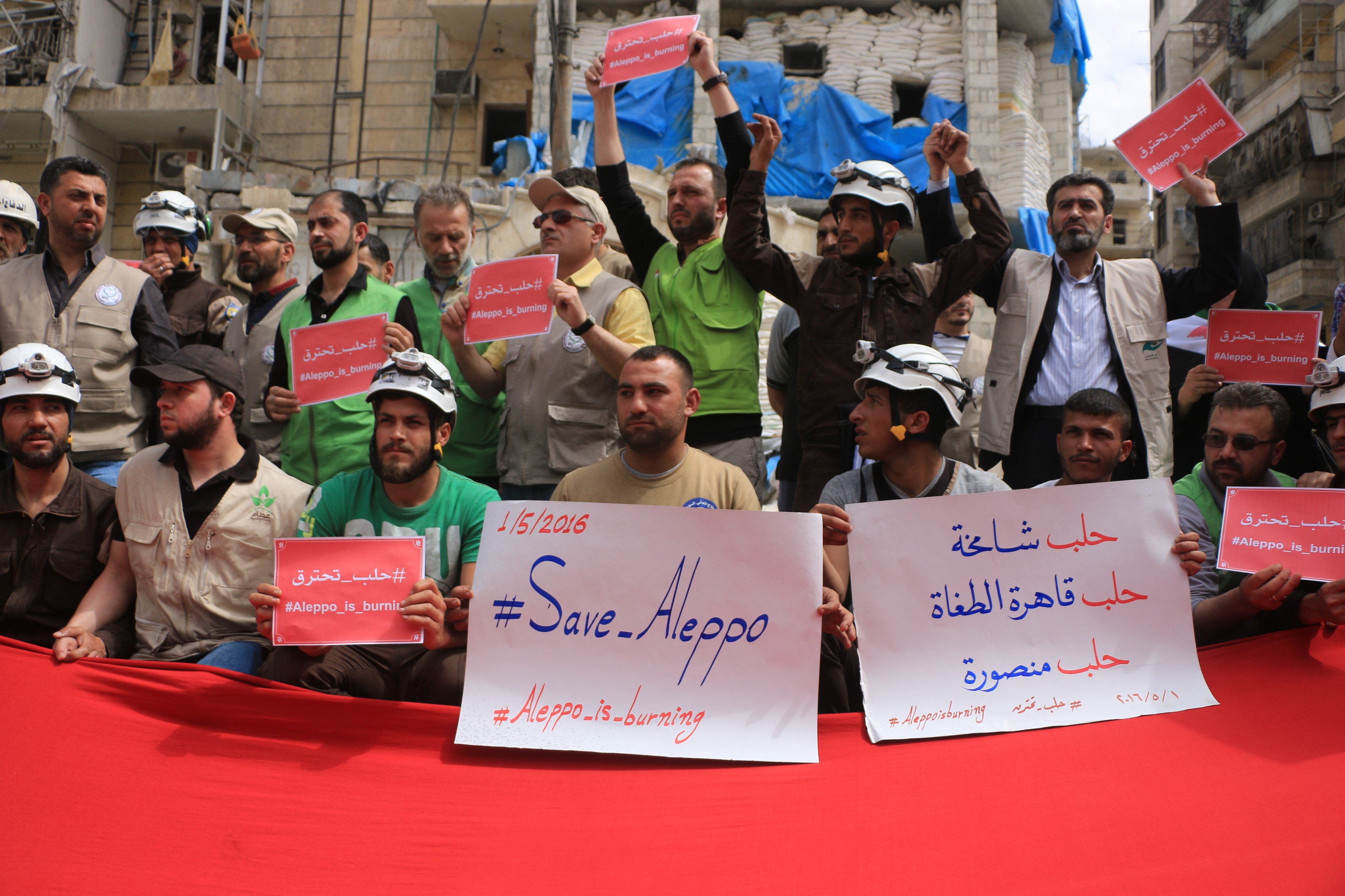 Syrians hold banners during a protest against Russian airstrikes on Jerusalem field hospital in the Sukkeri neighborhood of Aleppo, Syria, on May 1, 2016.