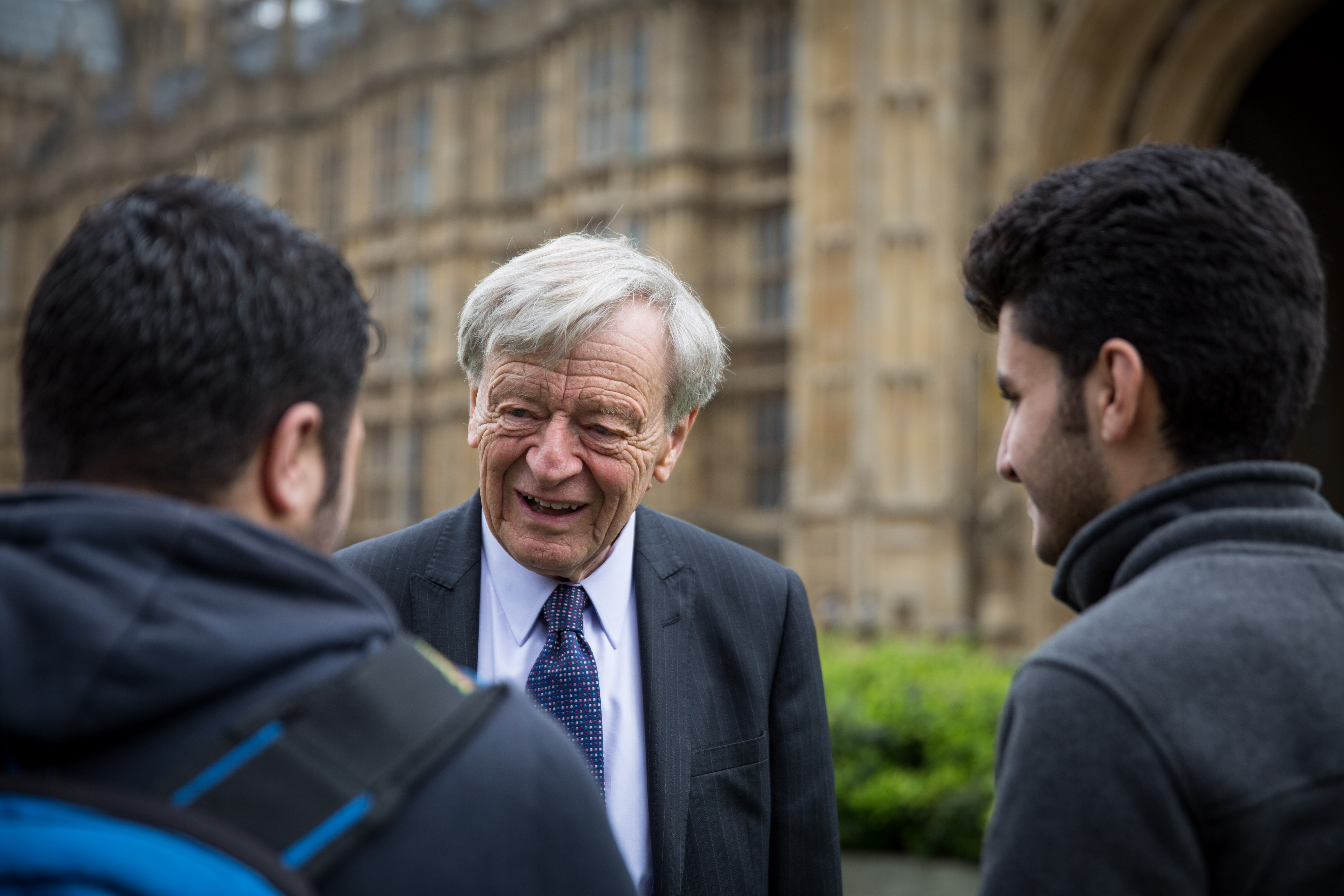 Lord Alf Dubs speaks to two child refugees from Syria on College Green on April 25, 2016 in London, England.