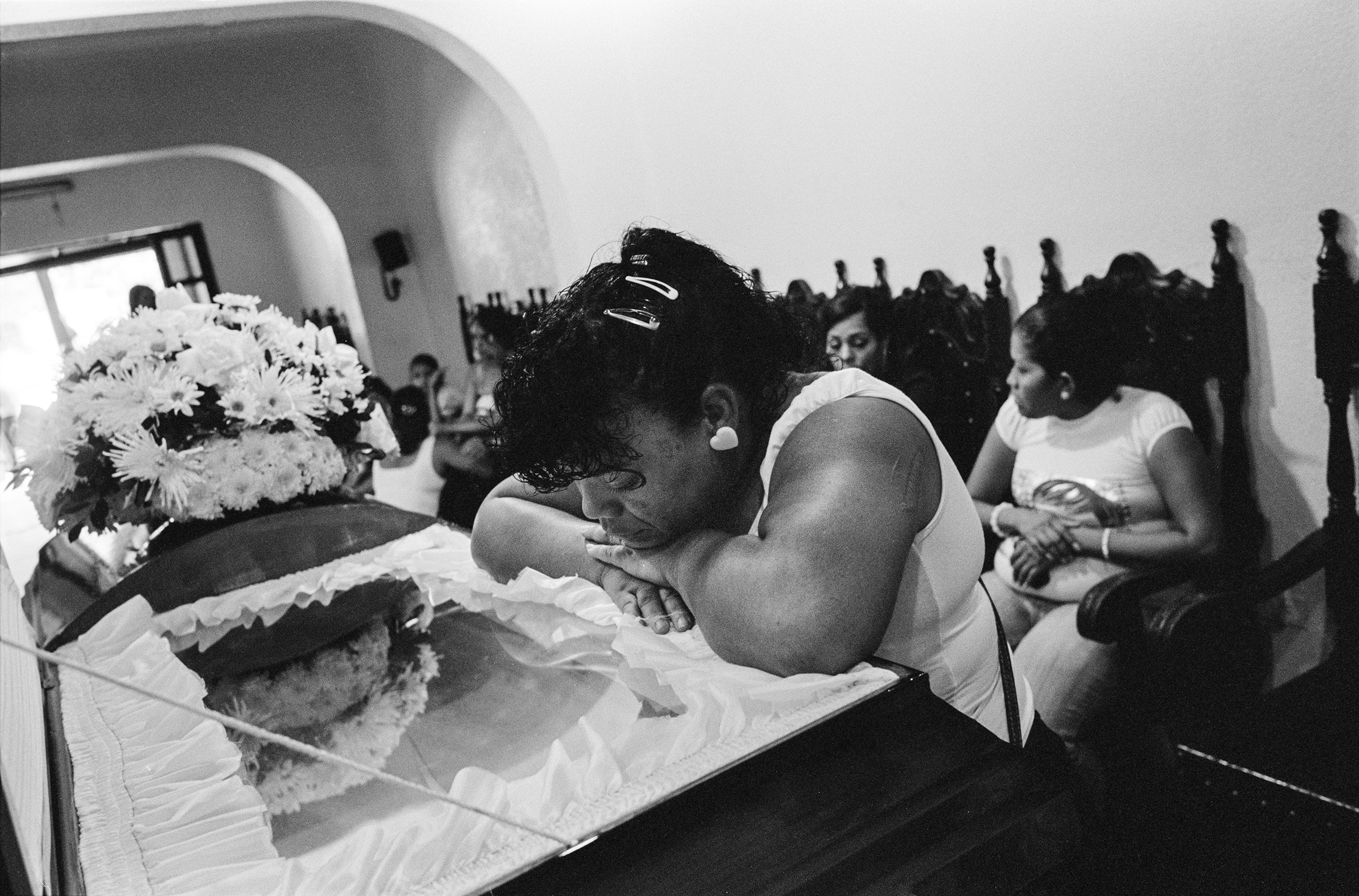 A family mourns at the funeral of a man who was shot dead with 16 bullets to the head, while coming out of his home with his daughter, by one of the  colectivos  of Caracas, November 2009. He was part of a rival gang.