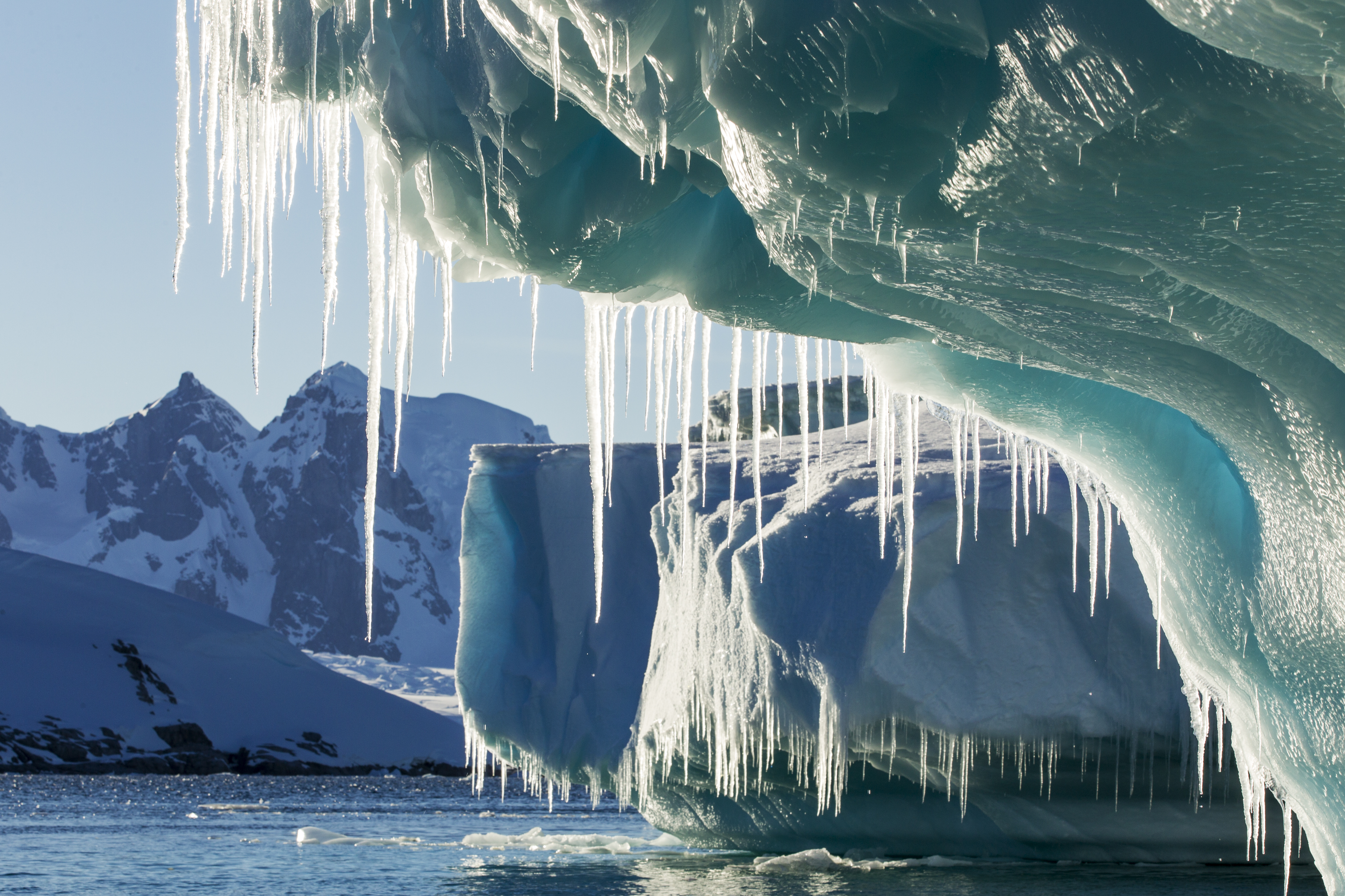 Antarctica, Petermann Island, Icicles hang from melting iceberg near Lemaire Channel