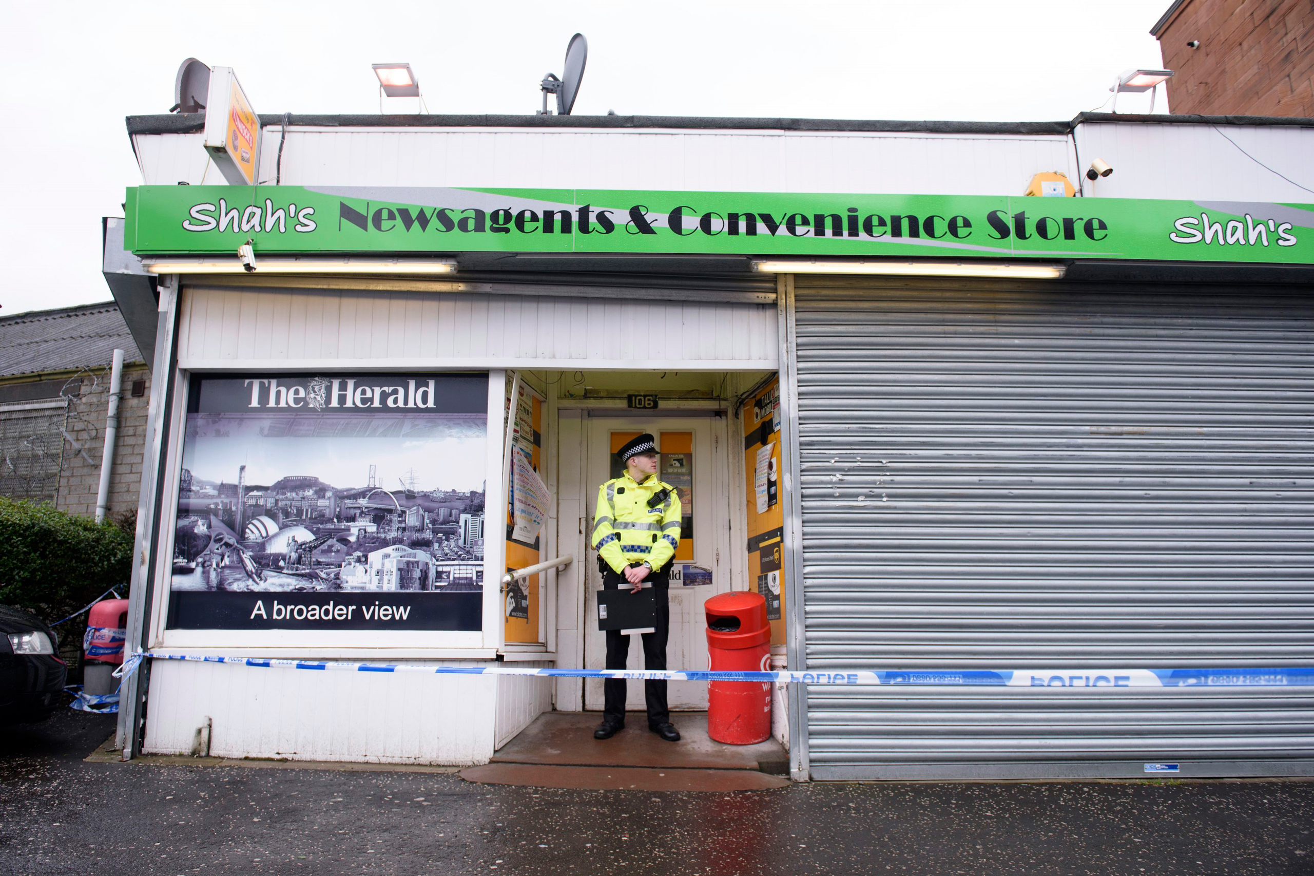"A police officer stands outside the shop where Asad Shah worked in Glasgow on March 26, 2016. Scottish police say the killing of a Muslim shopkeeper who wished Christians a happy Easter is being investigated as ""religiously prejudiced."""
