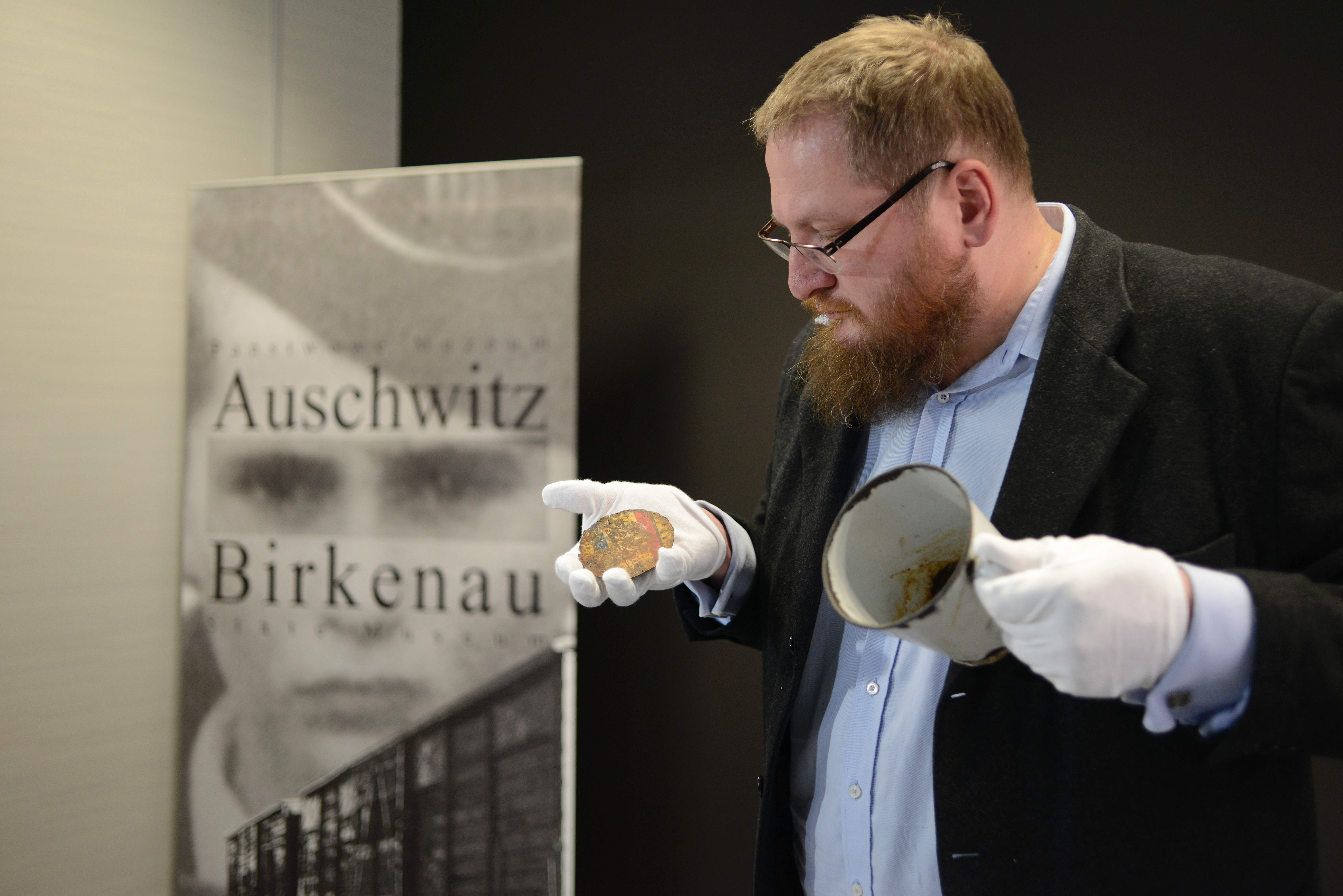 Piotr Cywinski, director of the Auschwitz-Birkenau museum, presents a metal mug with a double bottom in which a gold ring and necklace were found by employees of the museum in Oswiecim, Poland, May 19, 2016.