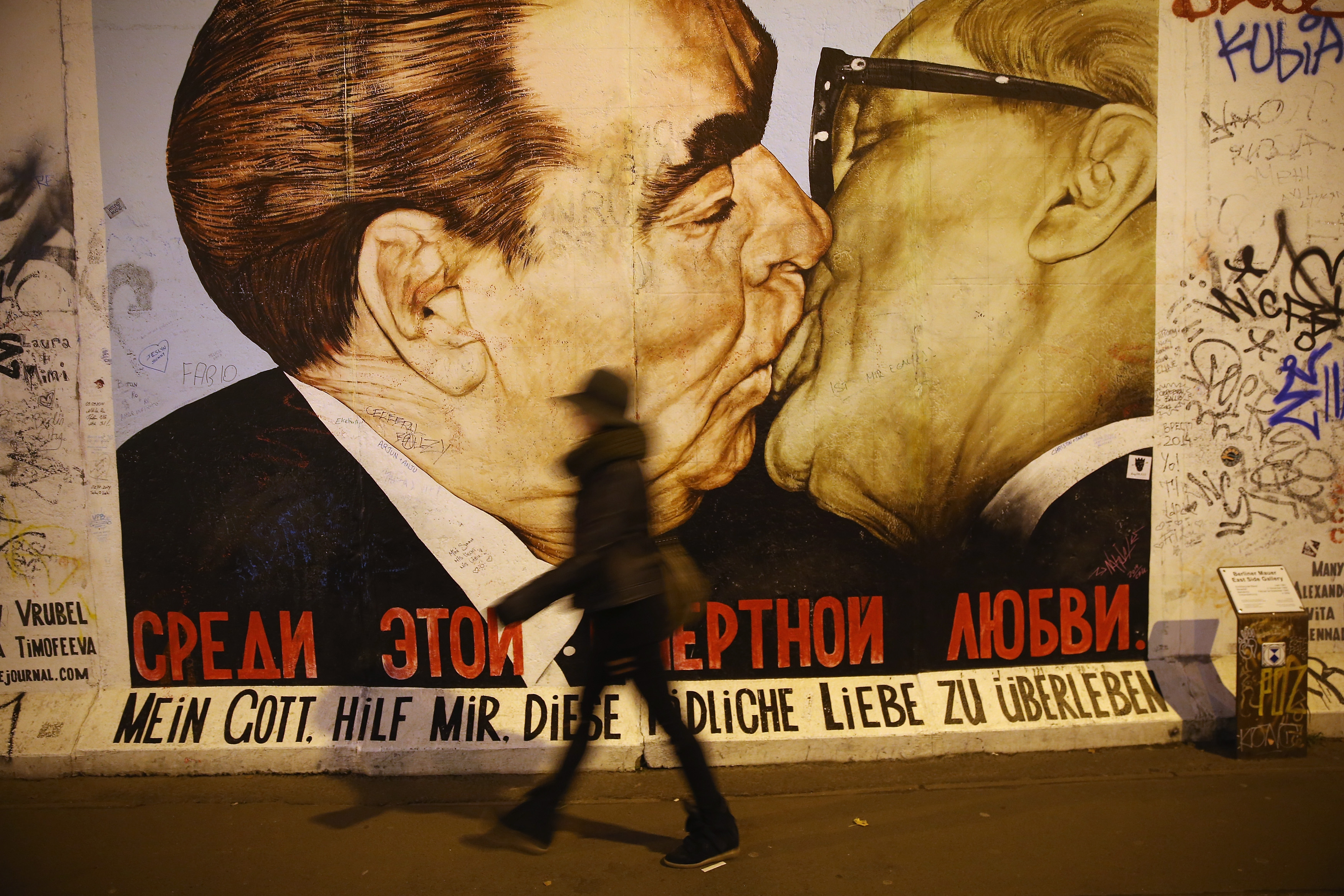 A visitor walks past a mural showing former Soviet leader Leonid Brezhnev (L) kissing former East German communist leader Erich Honecker by Russian painter Dmitri Vrubel at the East Side Gallery on Oct. 28, 2014 in Berlin, Germany.