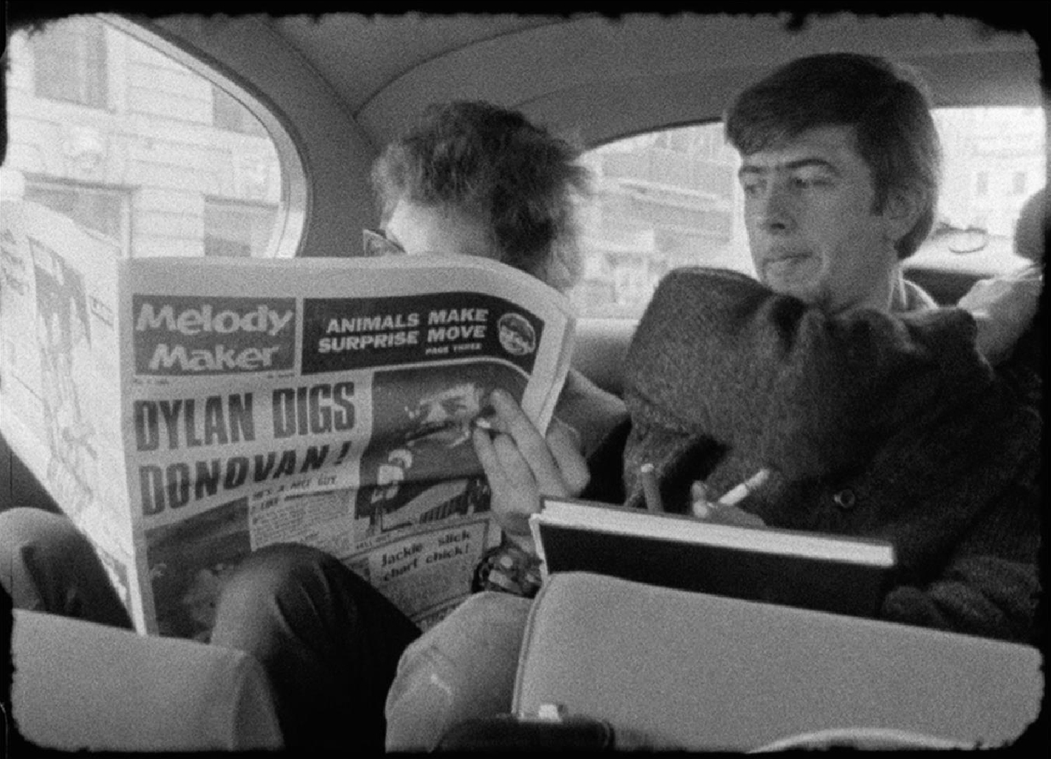 Bob Dylan reads Melody Maker, with John Mayall looking on, in London, 1965.
