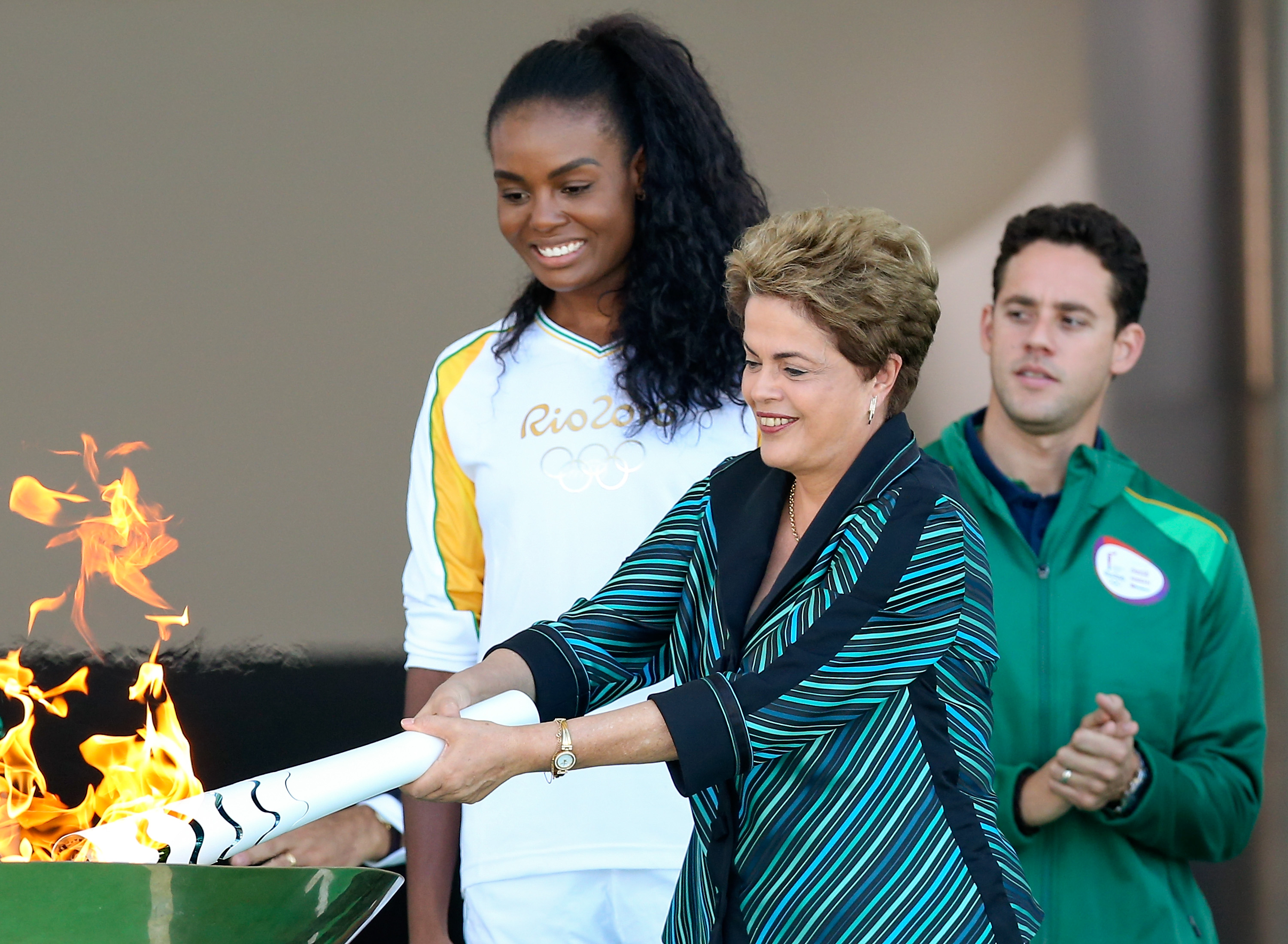 Dilma Rousseff, President of Brazil, lights the Olympic torch with the first torch bearer, volleyball player Fabiana Claudino at the Palacio do Planalto on May 3, 2016 in Brasilia, Brazil.