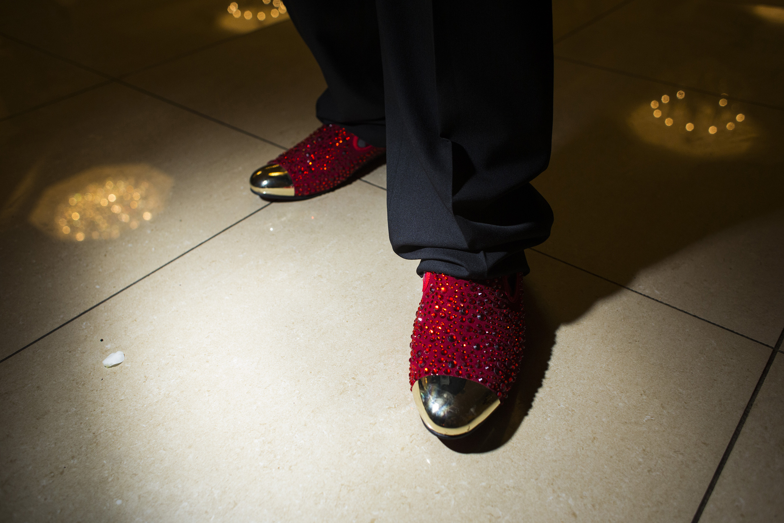 A Beecher High School student shows off his bejeweled red shoes during prom at the Signature Chop House in Flushing, Mich., May 20, 2016.