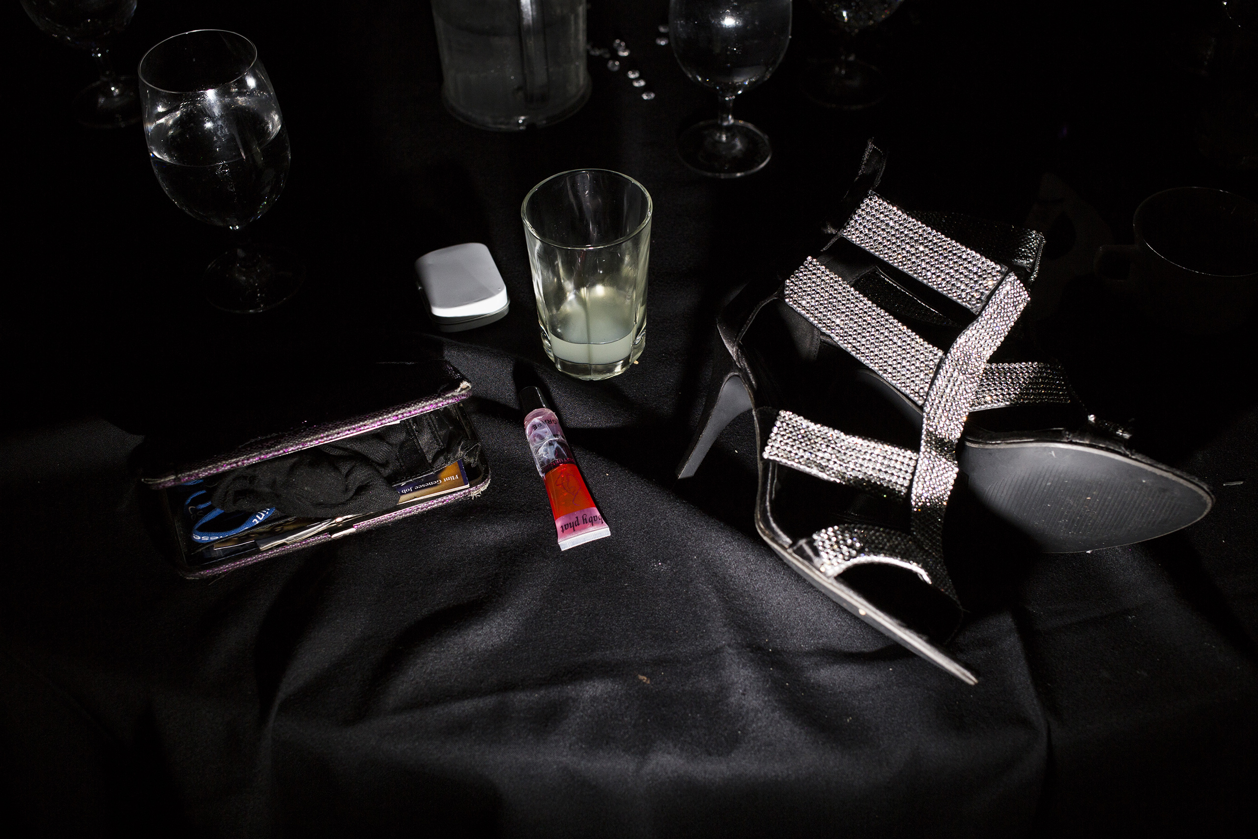 A wallet, lip gloss and shoes lay on a table as students dance at their prom, May 2015.