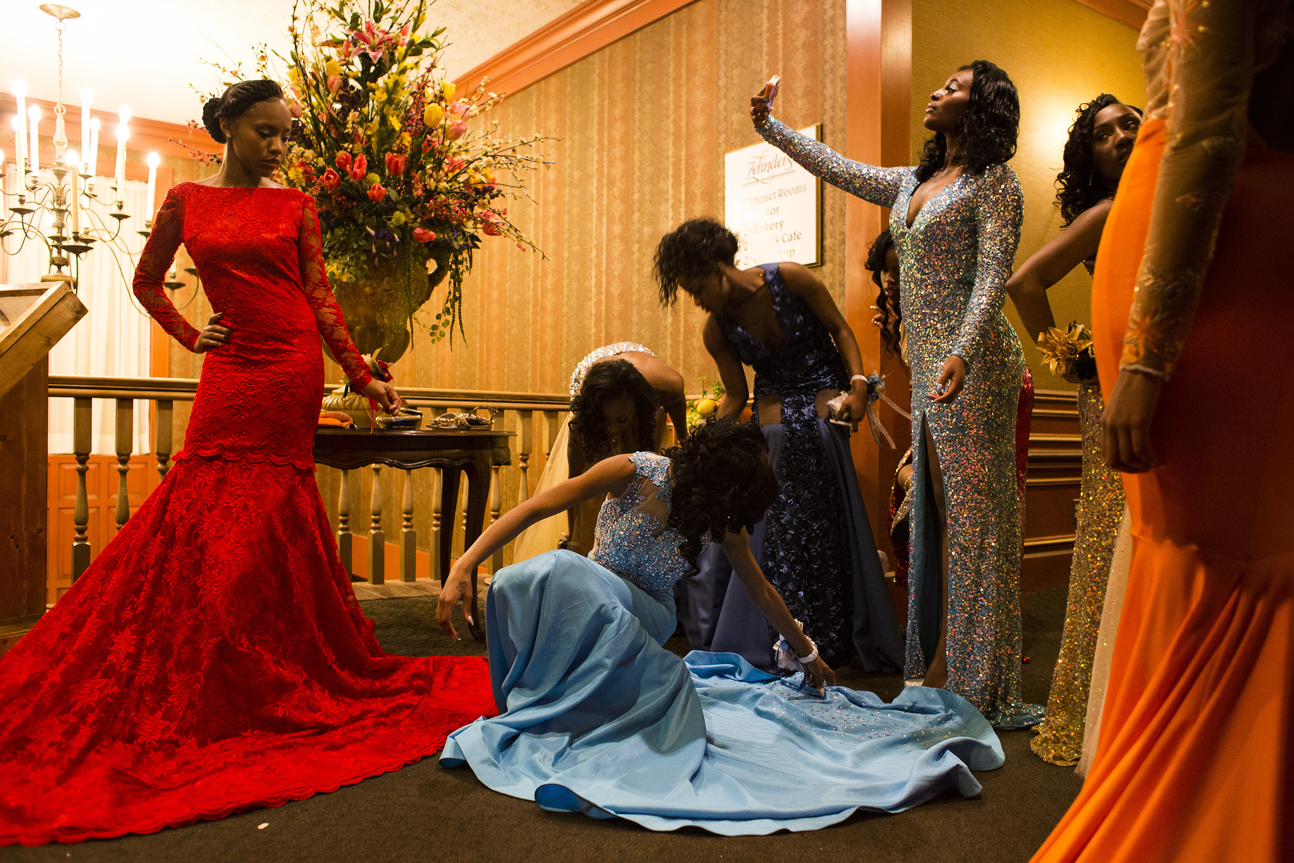 Toward the end of their prom night, girls attending Beecher High School's prom adjust their dresses before talking cell phone photos with friends and faculty, May 2015.