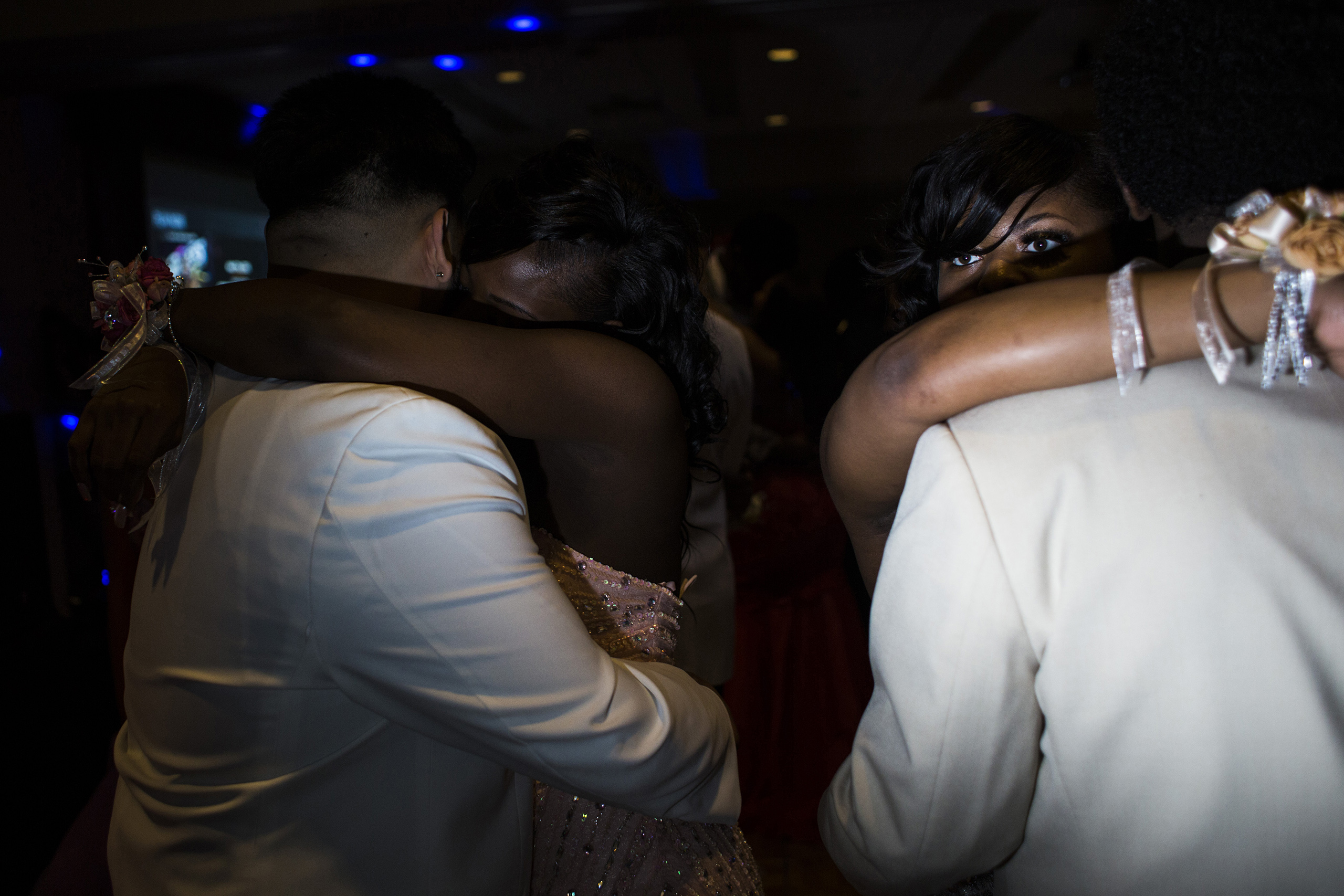 A Flint Southwestern Classical Academy student peers over her prom date's shoulder during a slow dance at the University of Michigan-Flint campus in downtown Flint, May 7, 2016. The theme was  Masquerade.