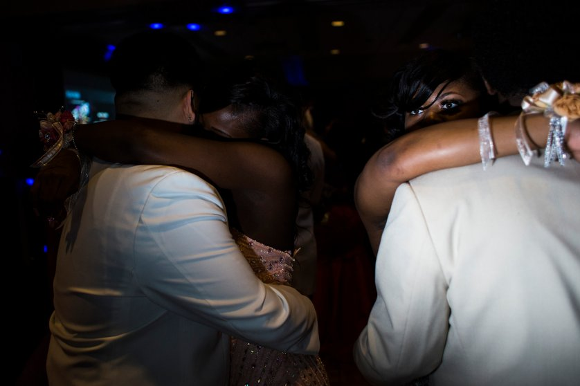 "A Flint Southwestern Classical Academy student peers over her prom date's shoulder during a slow dance at the University of Michigan-Flint campus in downtown Flint, May 7, 2016. The theme was ""Masquerade."""