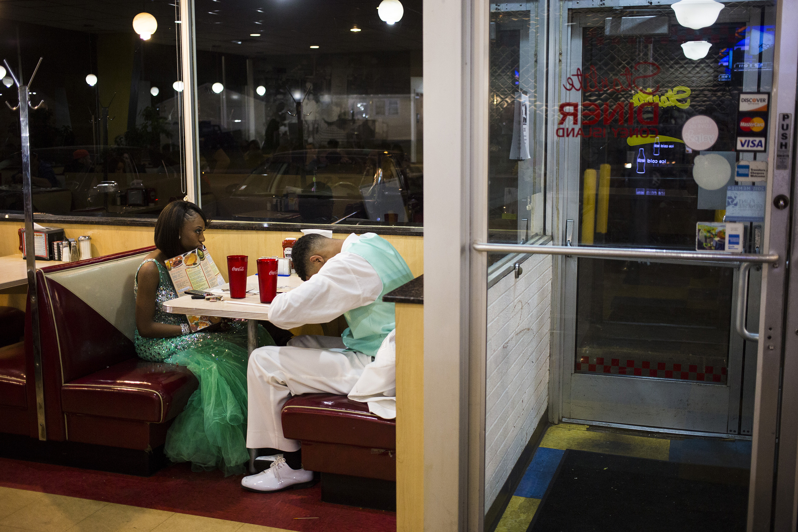 Northwestern High School senior Daryl Jones rests his head at the Starlite Diner & Coney Island while waiting for food with his date, Destiny Clements, following prom, May 2015.