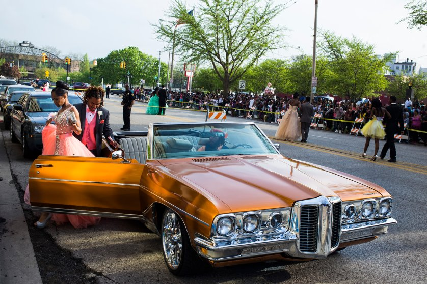 Flint Southwestern Classical Academy senior Reyna Deloney exits a car along with her date, Johnanthony Fulgham, while getting dropped off at their prom in downtown Flint, May 2015. Members of the community lined the closed-down street to cheer and take pictures.