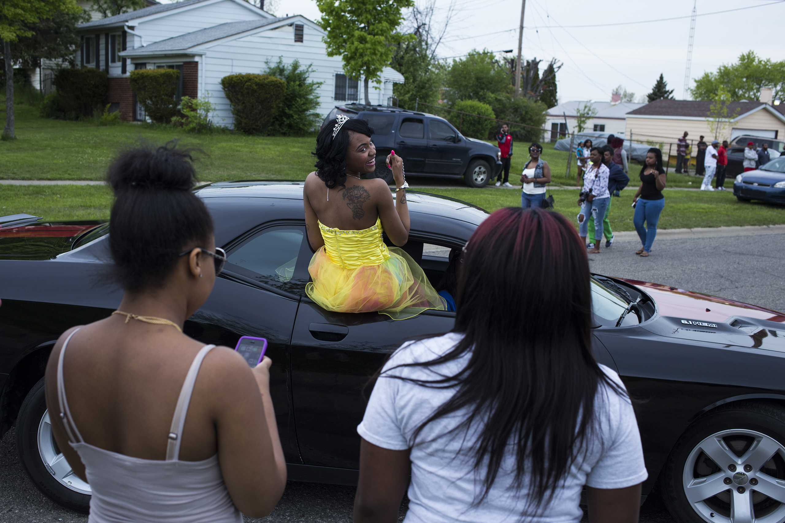 Beecher High School student Chatara Cornelius, 18, of Flint, Mich., dances from the window of a car as she makes her entry during a pre-prom red carpet-style event at Dailey Elementary School in Mount Morris, May 20, 2016.