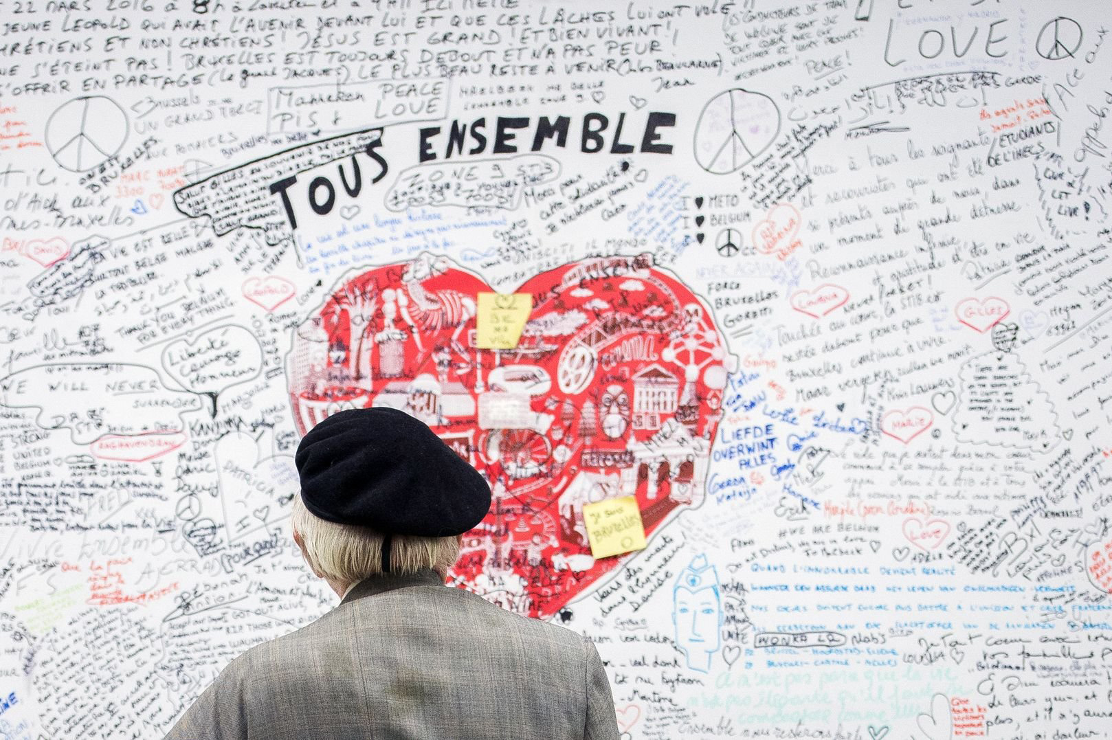 A man looks at a memorial panel for the victims of the March 22 attacks at the entrance of the Maelbeek-Maalbeek subway station in Brussels on May 11, 2016.