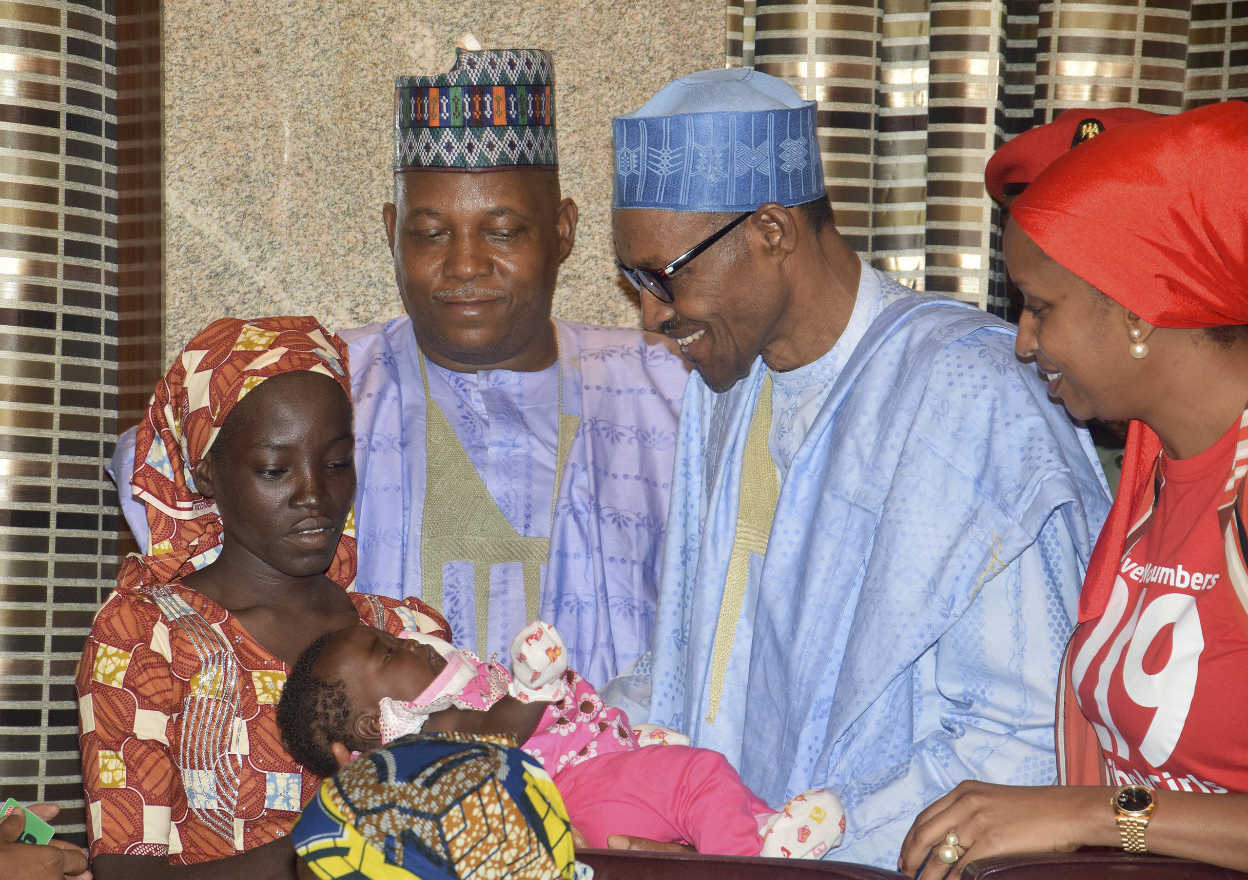 Nigerian President Muhammadu Buhari, second right, receives Amina Ali, the first rescued Chibok school girl, at the Presidential palace in Abuja, Nigeria, May. 19, 2016.