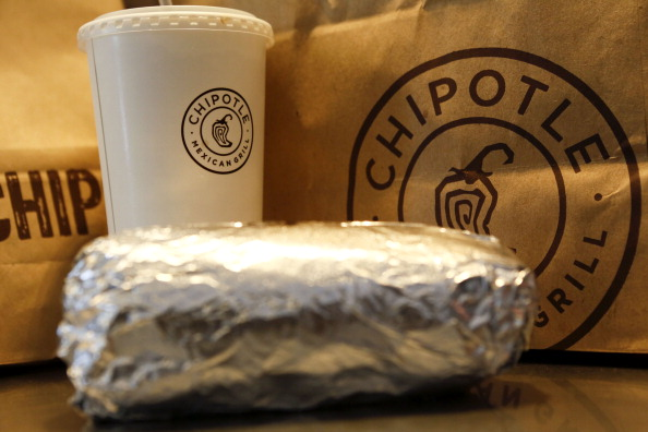 A steak burrito is arranged for a photograph with a drink and bags of chips at a Chipotle Mexican Grill Inc. restaurant in Hollywood, California, U.S., on Tuesday, July 16, 2013.