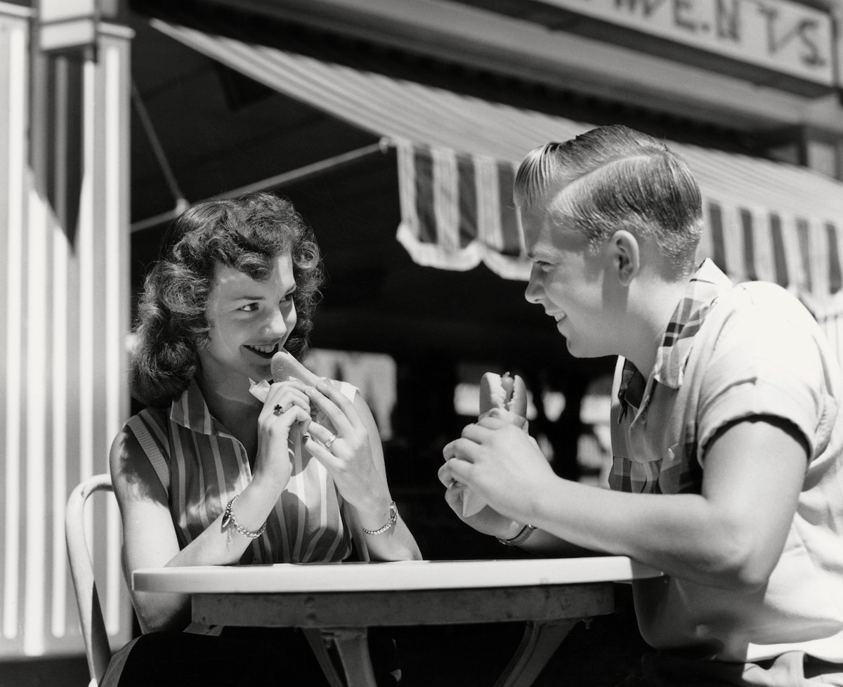 Teenage couple eating hotdogs outside at refreshment stand table, circa 1950