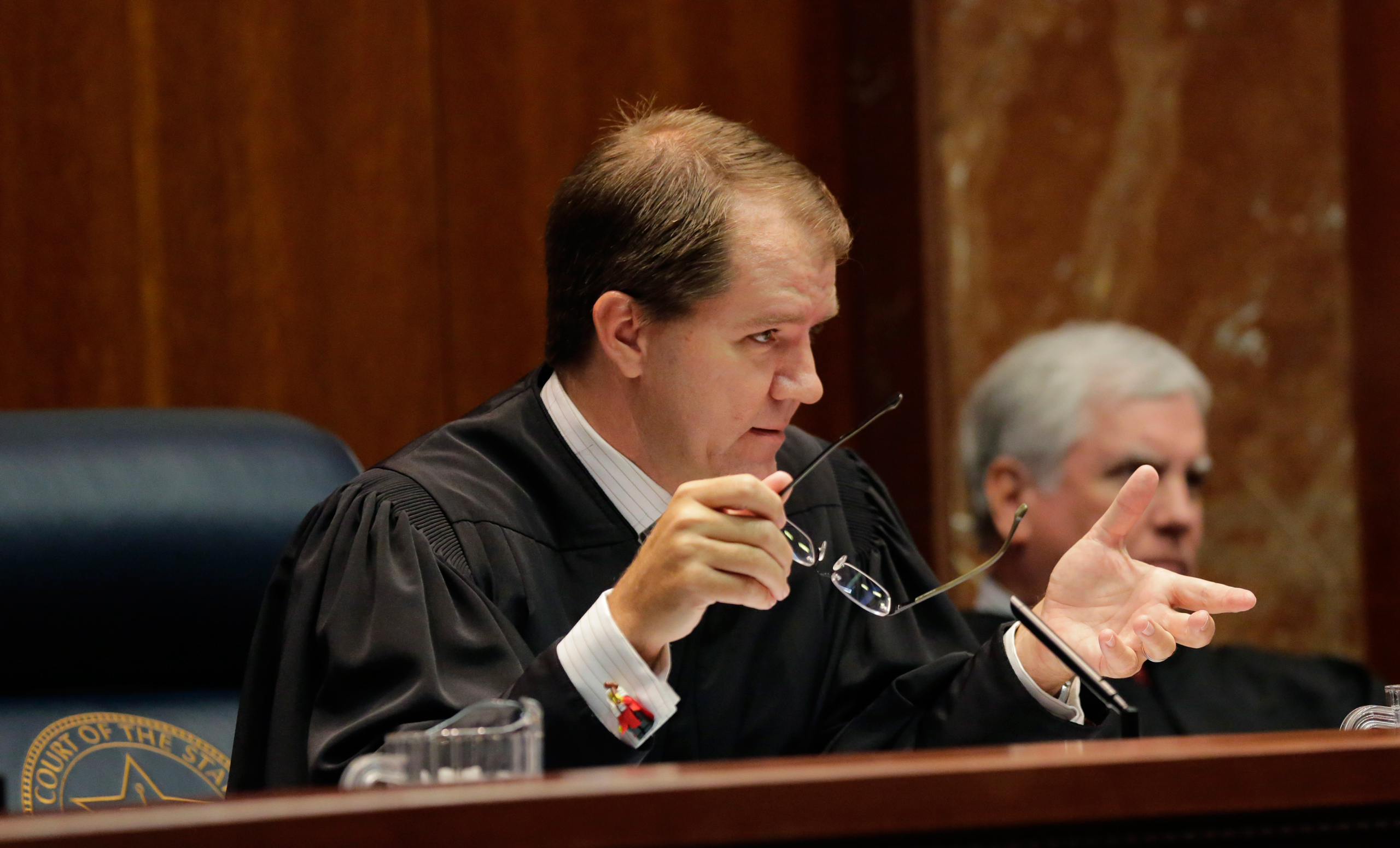 Texas Supreme Court Justice Don Willett, left, asks a question during oral arguments in Texas' latest school finance case at the state Supreme Court, Tuesday, Sept. 1, 2015, in Austin, Texas. Attorneys for more than 600 school districts suing Texas argue that the funding is inadequate and unfairly distributed, making it hard for students and schools to meet stringent academic standards. Attorney General Ken Paxton's office counters that, while not perfect, public education money meets state constitutional requirements for an efficient system providing a  general diffusion of knowledge. (AP Photo/Eric Gay)